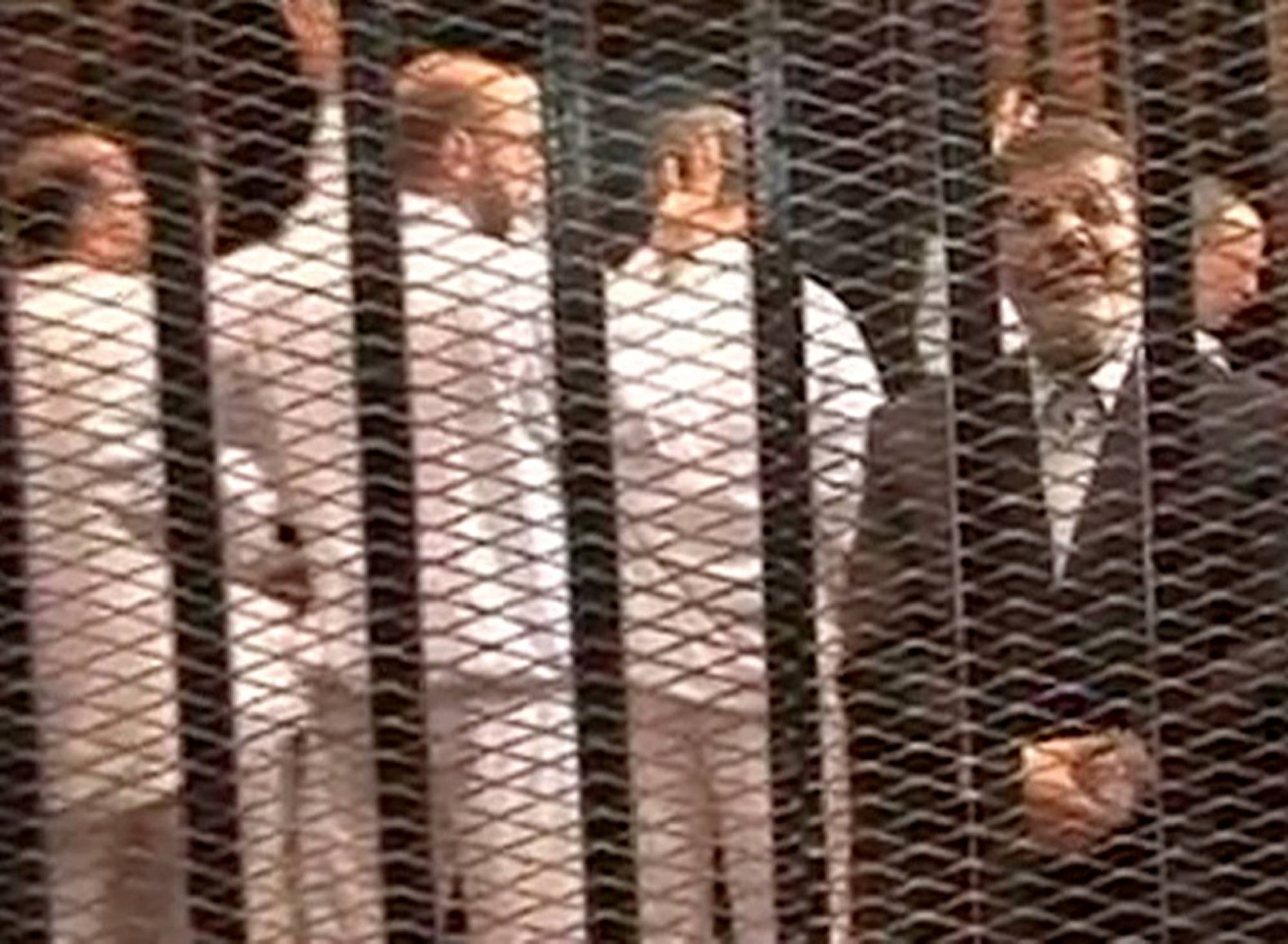 Ousted President Mohammed Morsi, right, is seen speaking from the defendant's cage as he stands with co-defendants in a makeshift courtroom during a trial hearing in Cairo, Egypt, in November 2013. Egypt's crackdown on Islamists has jailed 16,000 people over the past eight months in the country's biggest round-up in nearly two decades, according to previously unreleased figures from security officials.