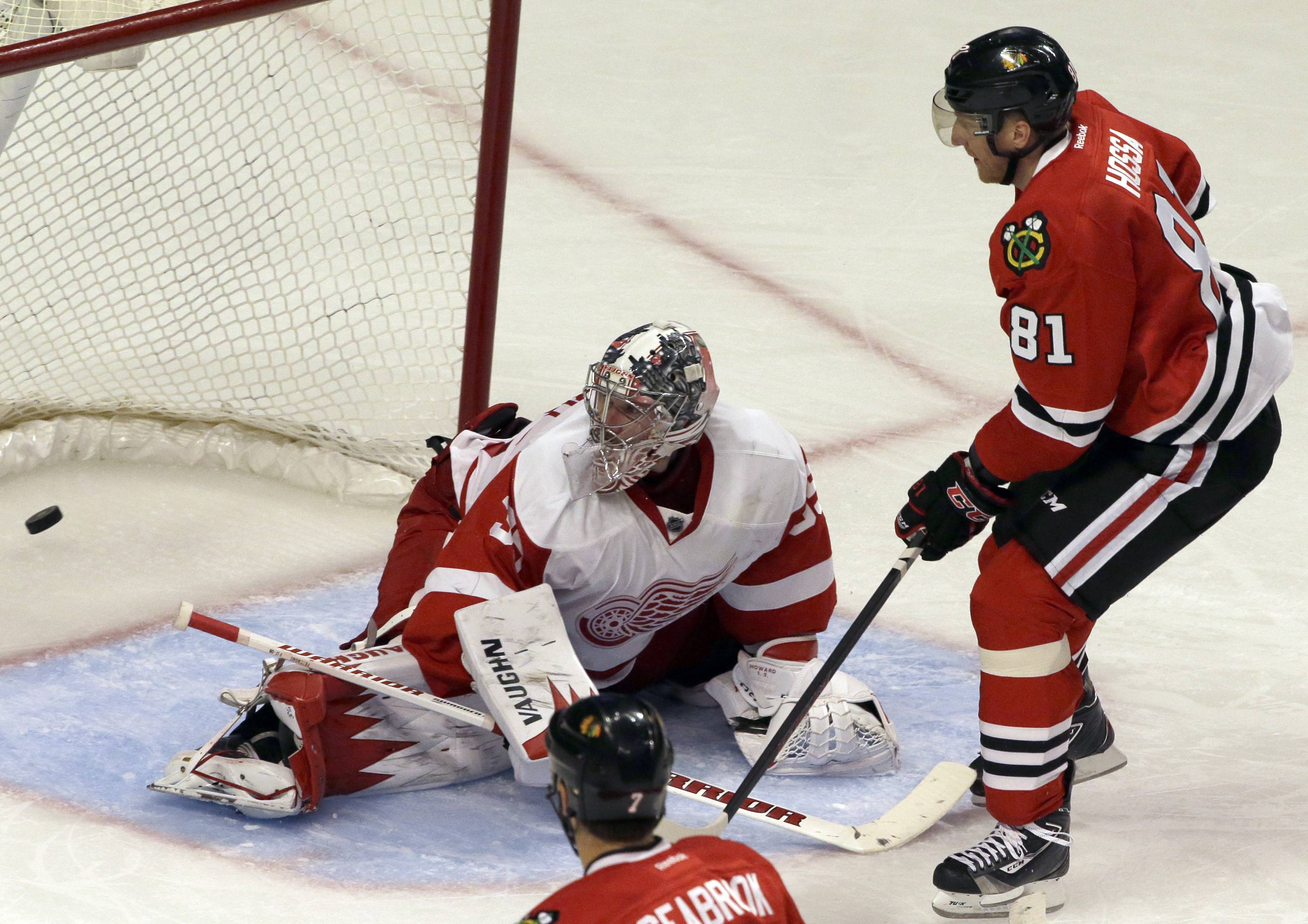 The Blackhawks' Marian Hossa scores against Red Wings goalie Jimmy Howard in the third period Sunday. Hossa also had a pair of assists.