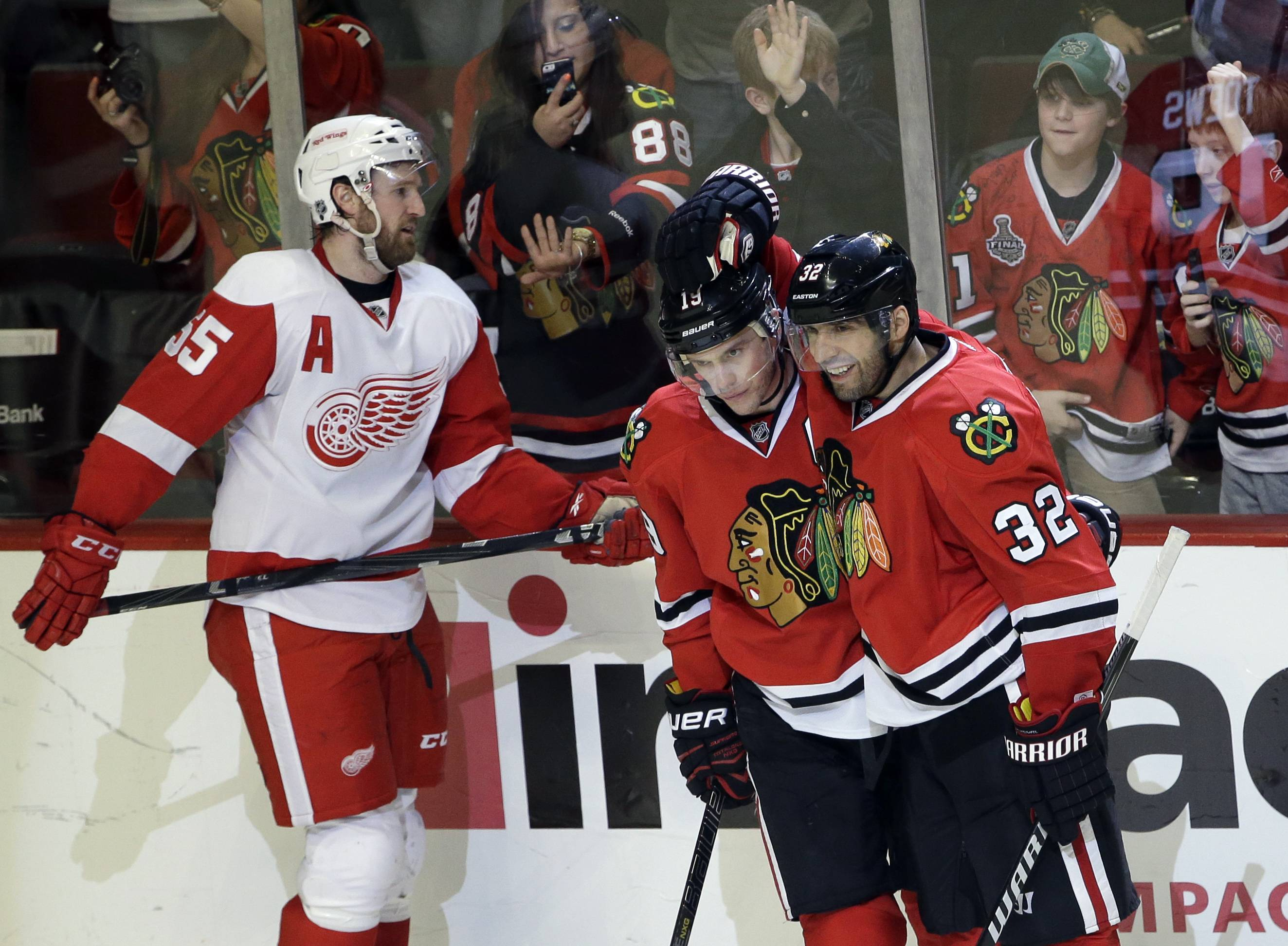 Blackhawks center Jonathan Toews (19) celebrates with Michal Rozsival (32) after scoring his goal as Detroit Red Wings' Niklas Kronwall (55) reacts during the third period of an NHL hockey game in Chicago, Sunday, March 16, 2014. The Blackhawks won 4-1.
