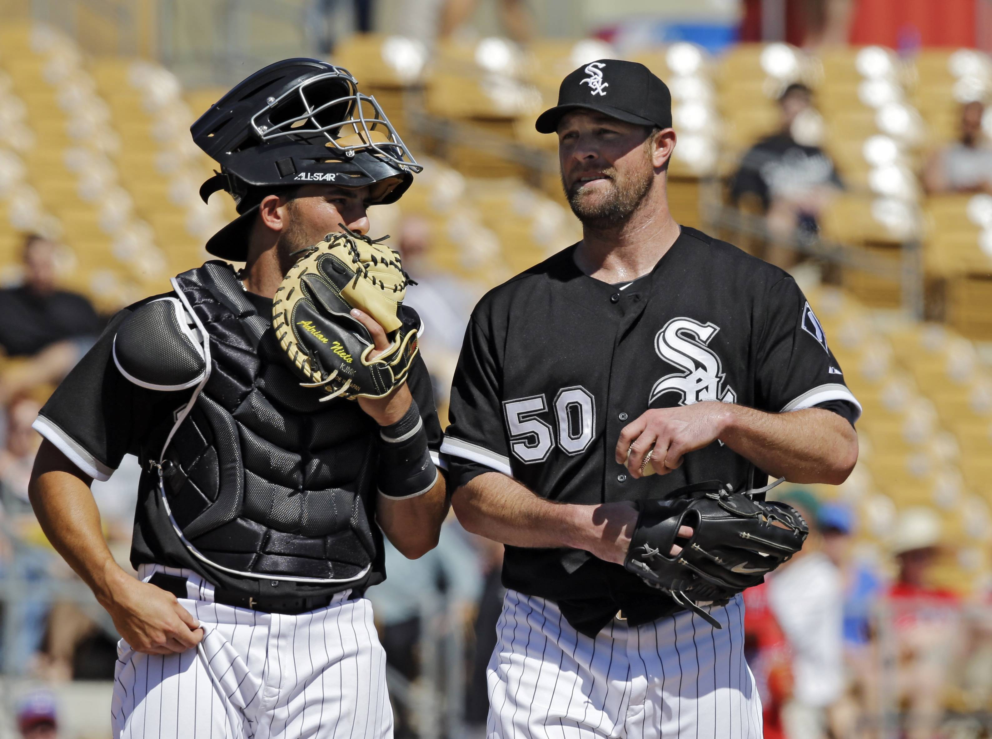 Adrian Nieto, who is battling for the backup catcher's job, confers with starting pitcher John Danks on Sunday.