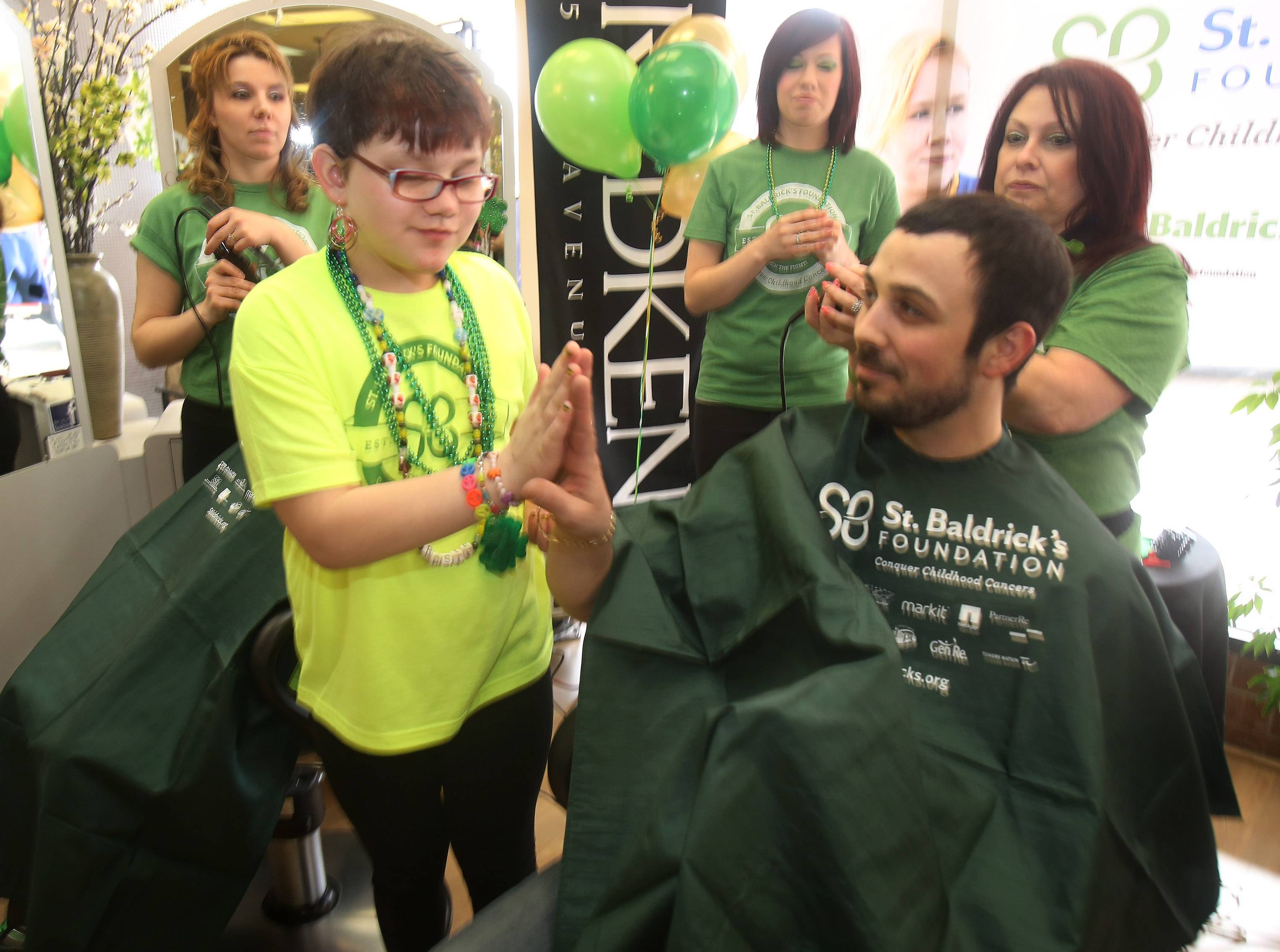 Rosie Colucci, 9, of Palatine high-fives Chris Galie of Algonquin before he gets his head shaved during a St. Baldrick's event Sunday in Lake Zurich. Rosie was the guest of honor at the event, in which participants get donations for cancer research by pledging to shave their heads. Organizers were hoping to raise up to $10,000.
