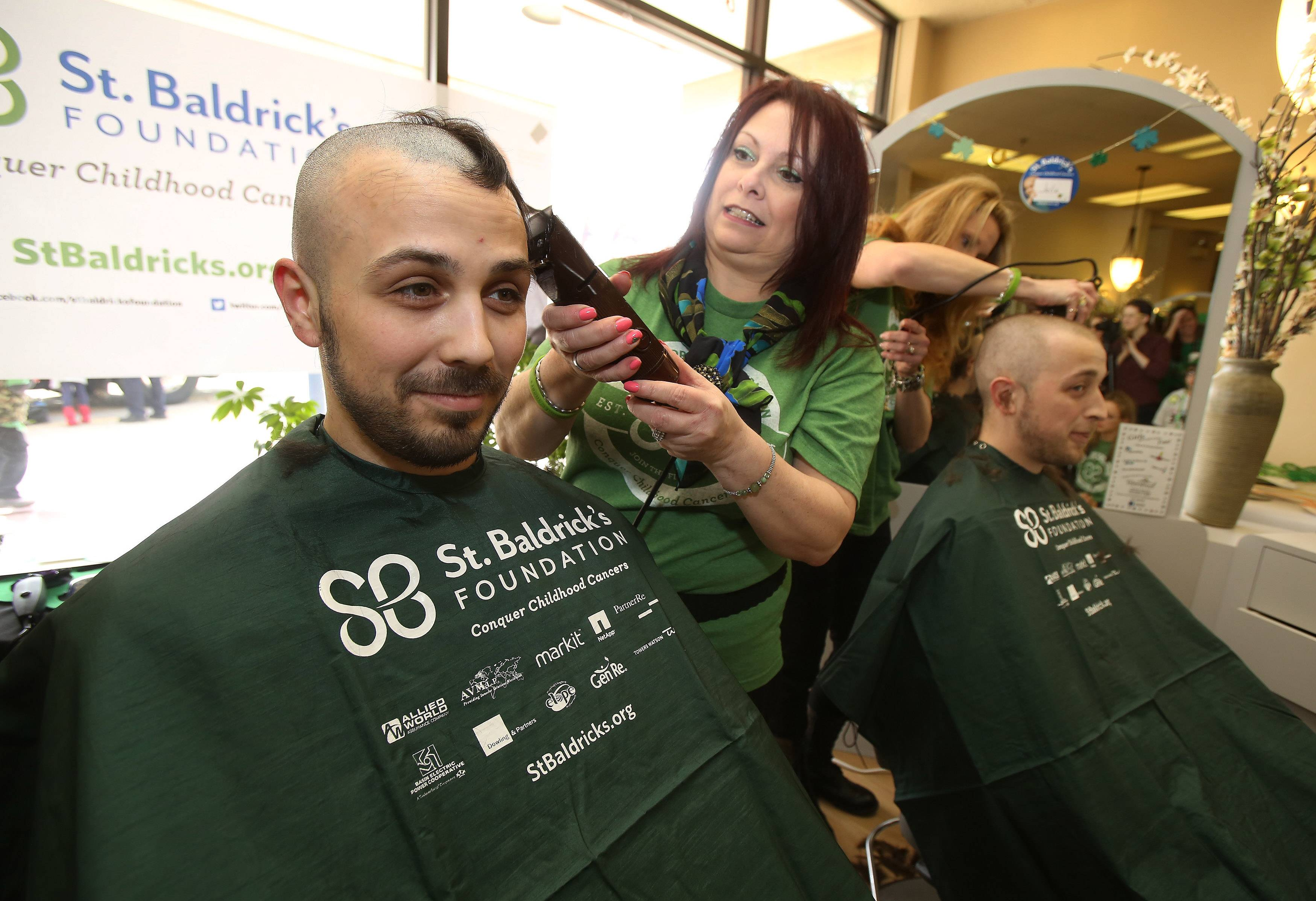 Brothers Chris, left, and Myles Galie of Algonquin have their heads shaved by stylists Mare Cichy and Julia Goings during a St. Baldrick's fundraiser Sunday at International Hair Designs in Lake Zurich. The event was in honor of cancer patient Rosie Colucci, 9, of Palatine.