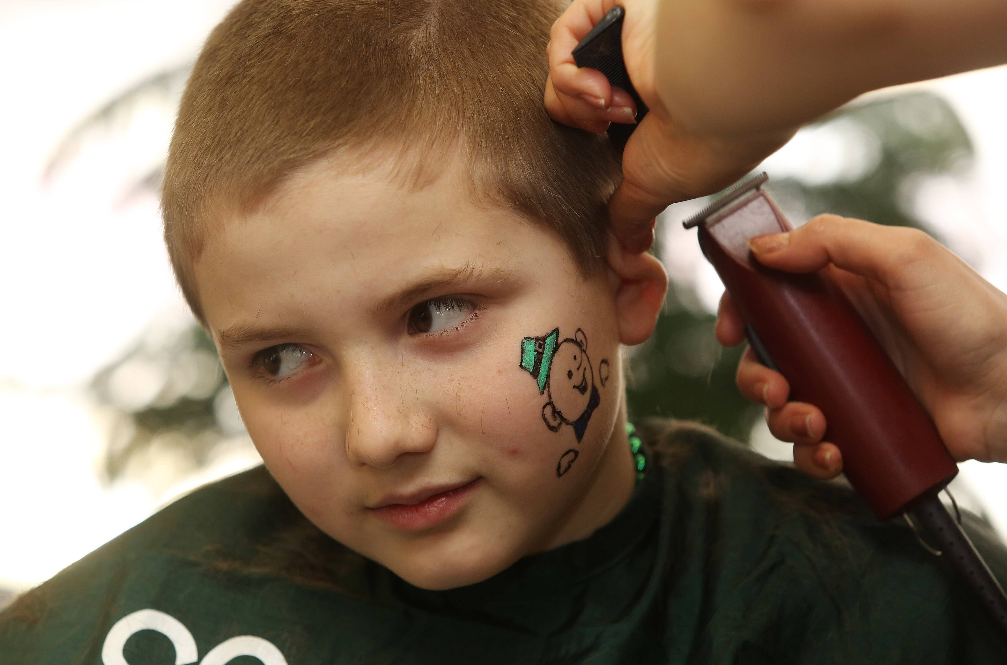 Jason Sabatino, 10, of Carpentersville has his head shaved during a St. Baldrick's fundraiser Sunday at International Hair Designs in Lake Zurich. The event was in honor of cancer patient Rosie Colucci, 9, of Palatine.