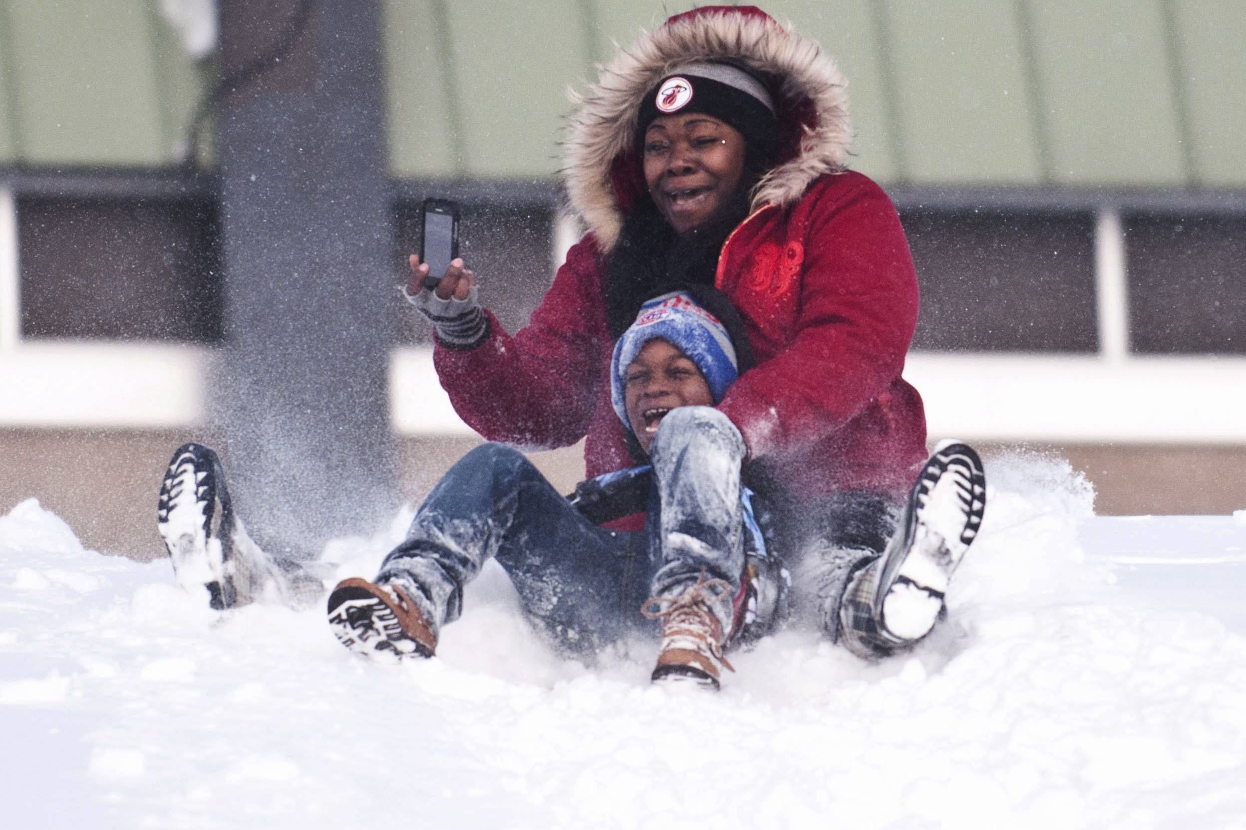 Sharrissa McKinzie, of Flint, sleds down a hill with her son Detrayvion McKinzie, last week. Another round of snow and ice is forecast for the Midwest and Mid-Atlantic.