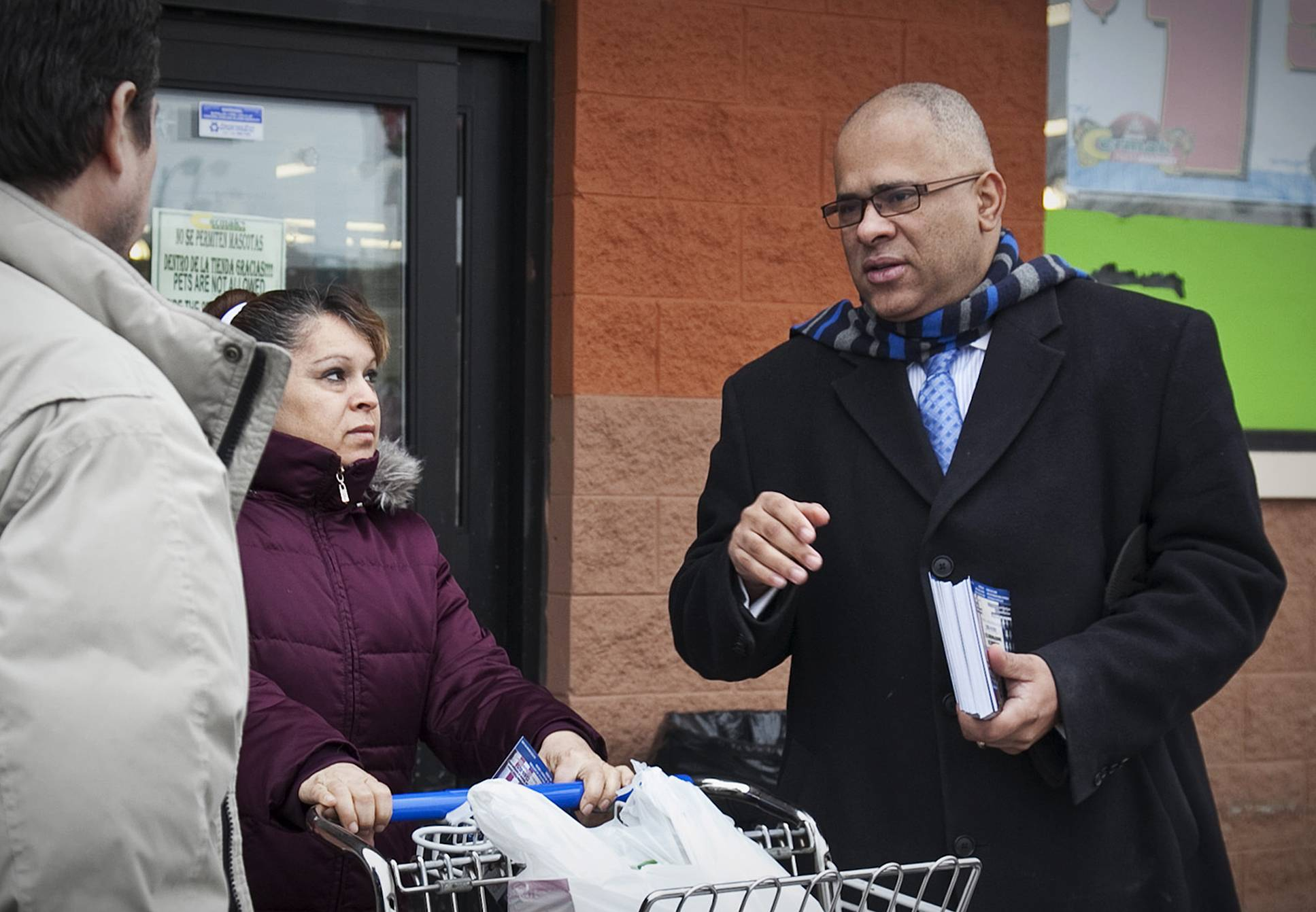 In this Jan. 30, 2014 photo, Tio Hardiman, the former head of CeaseFire Chicago, campaigns for the Democratic nomination for Illinois governor, outside a produce store in Chicago. Hardiman faces incumbent Gov. Pat Quinn in the March 18 primary. Quinn and running mate former Chicago Public Schools CEO Paul Vallas have declined campaign interviews in 2014 and Quinn has virtually ignored Hardiman. The anti-violence activist has camped out outside Quinn's home and campaign headquarters to demand debates, but neither Quinn nor his campaign has answered him.