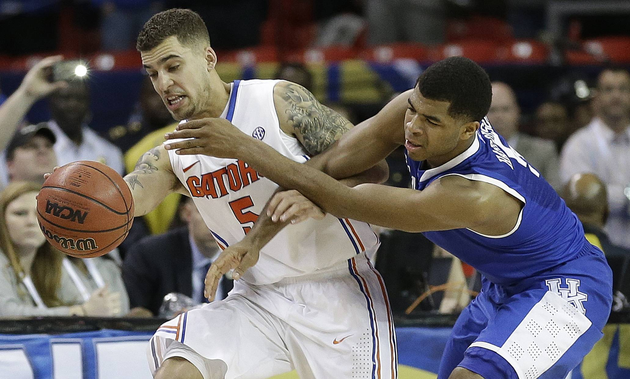 Kentucky guard Andrew Harrison (5) and Florida guard Scottie Wilbekin (5) work for a loose ball during the second half of an NCAA college basketball game in the Championship round of the Southeastern Conference men's tournament, Sunday, March 16, 2014, in Atlanta. Florida won 61-60.