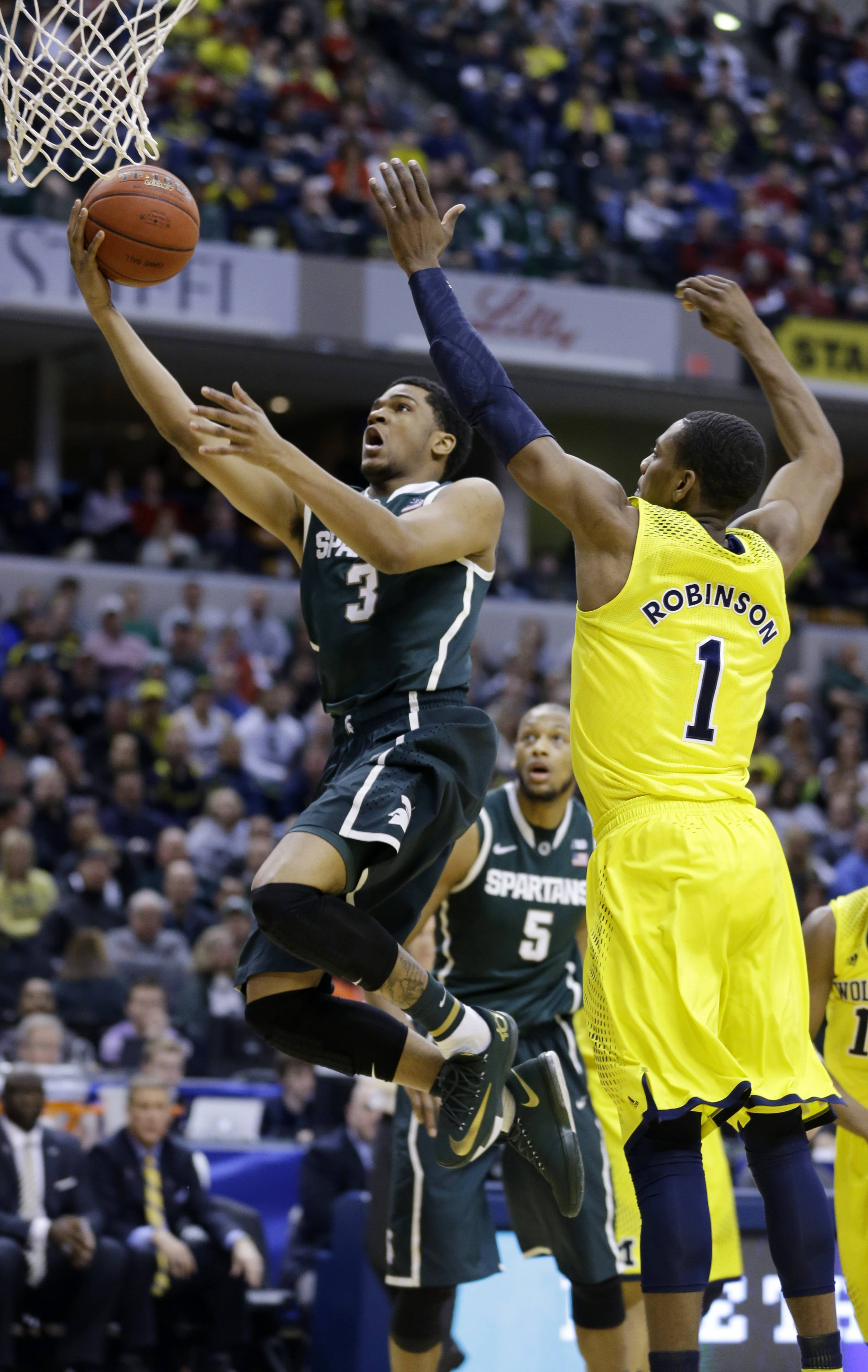 Michigan State guard Alvin Ellis III (3) goes up for a basket against Michigan forward Glenn Robinson III (1) in the first half of an NCAA college basketball game in the championship of the Big Ten Conference tournament on Sunday, March 16, 2014, in Indianapolis.