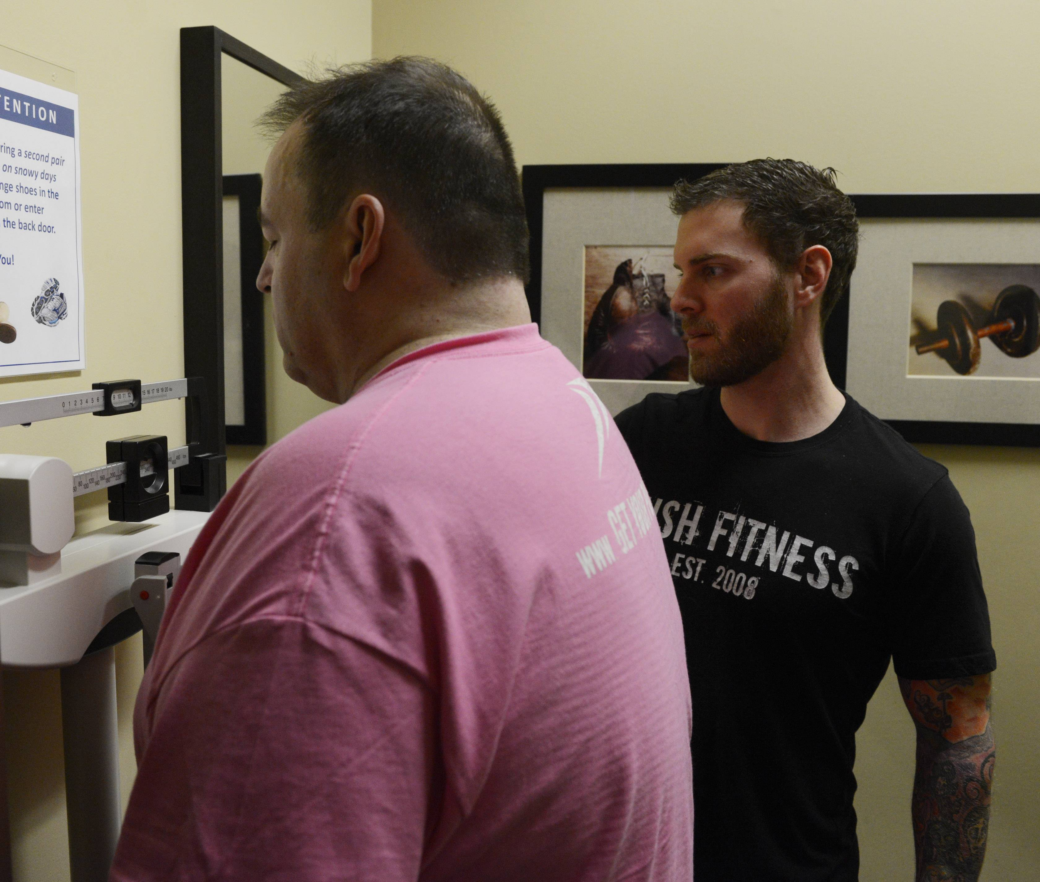 Every boot camp at Push Fitness in Schaumburg ends with the weekly weigh-in. Trainer Brad Parotto checks the numbers as John Bohanek weighs in — after four weeks he is down 29 pounds.