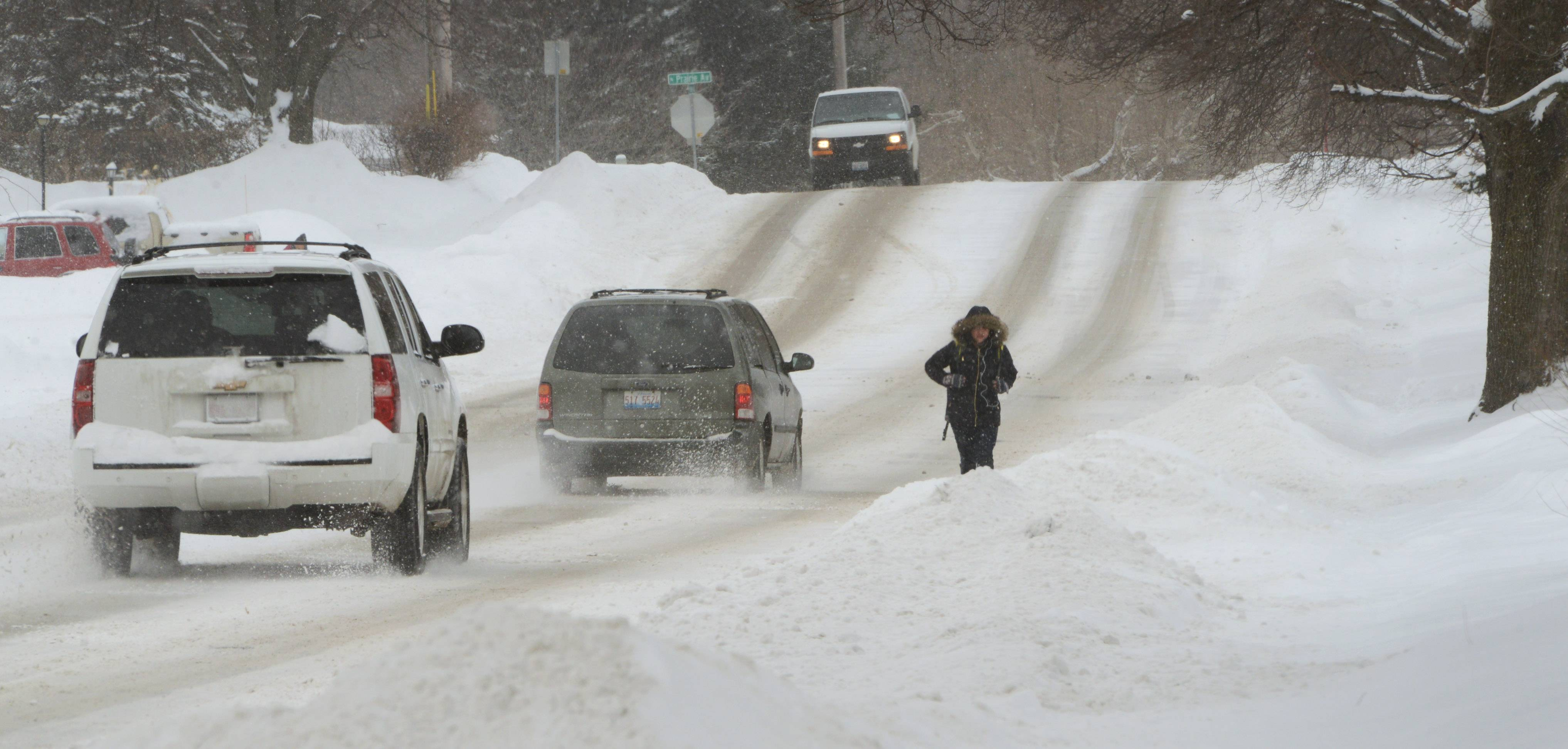 A pedestrian finds it easier to walk on the road than the sidewalk along Hawley Street, just west of Route 45 in Mundelein, after a recent storm.