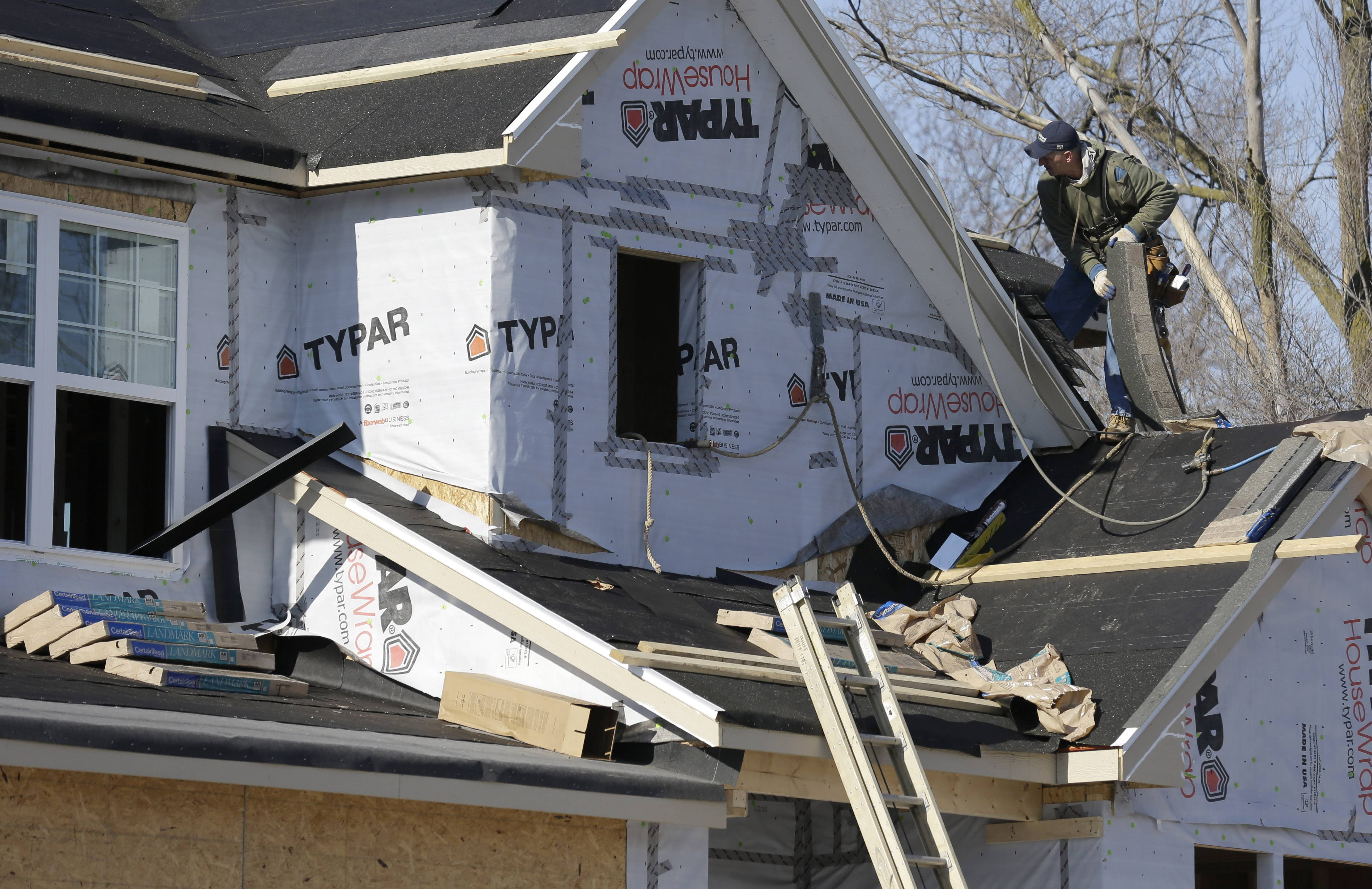 A builder works on the the roof of a new home under construction in Wilmette.