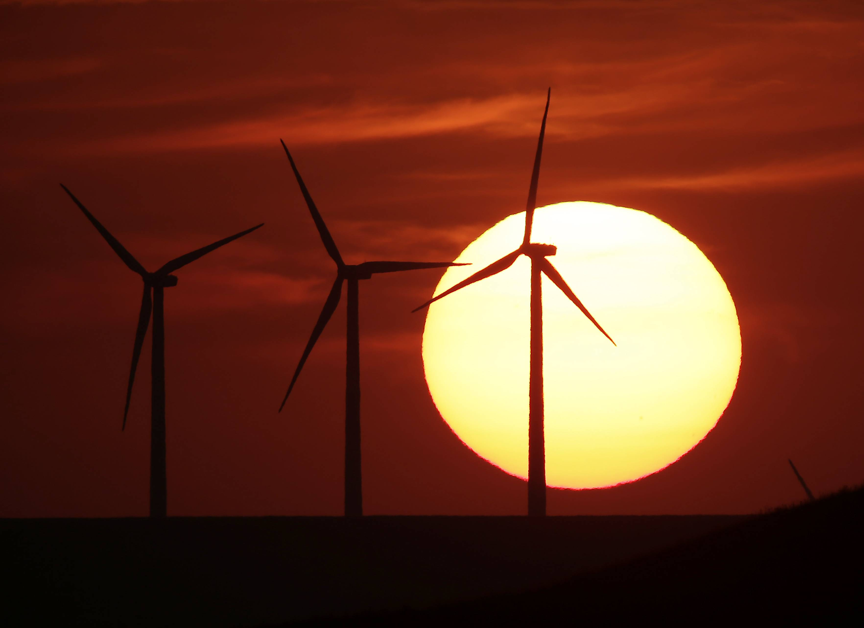 Wind turbines are silhouetted by the setting sun as they produce electricity near Beaumont, Kan.