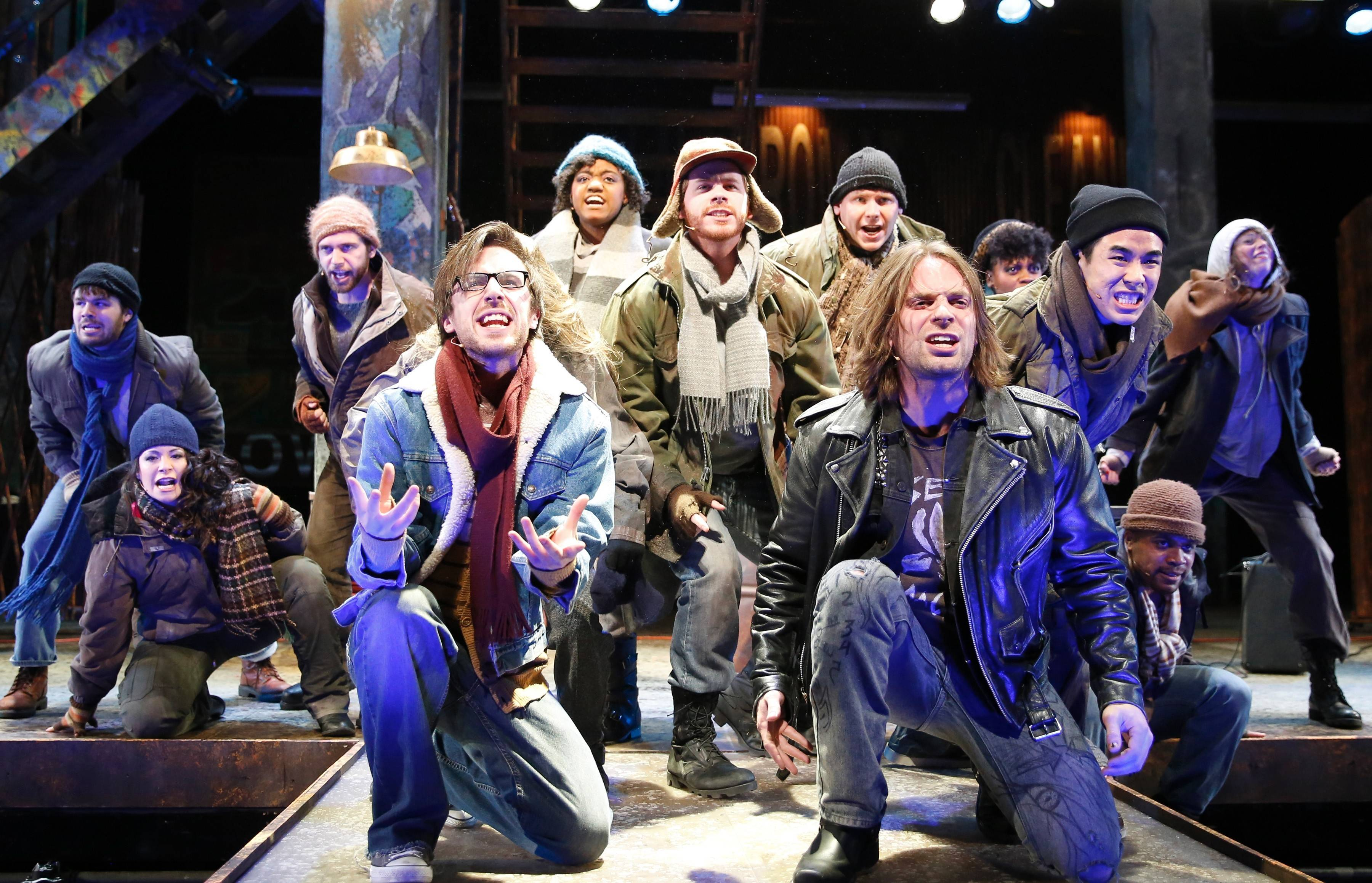 "Mark (Andrew M. Mueller), left front, and Roger (Adam Michaels) lead the ensemble in the title number ""Rent"" at the Paramount Theatre in Aurora. The production runs through Sunday, April 6."