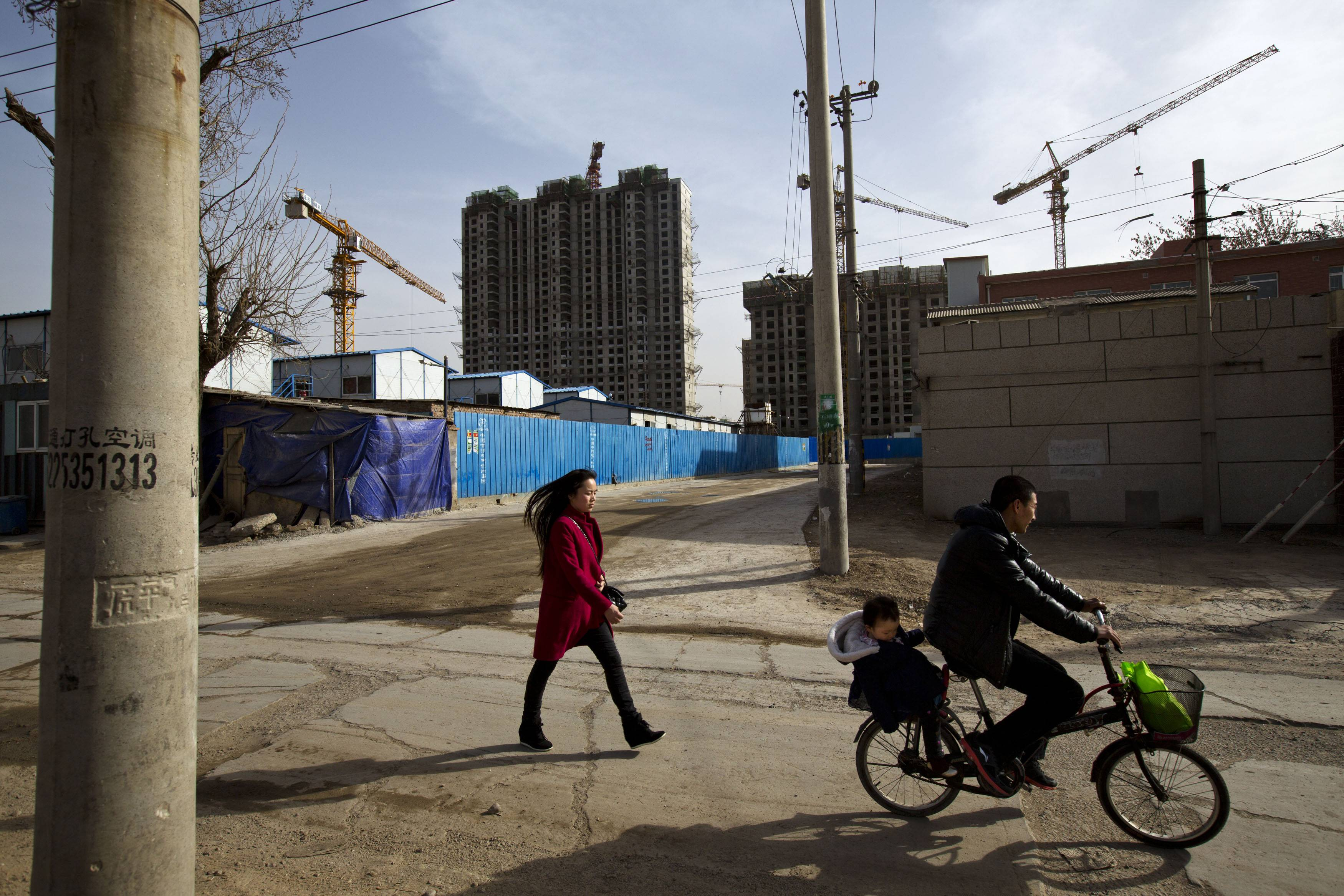 A migrant worker's family heads their way home near a construction site of a residential real estate project in a village on the outskirts of Beijing.