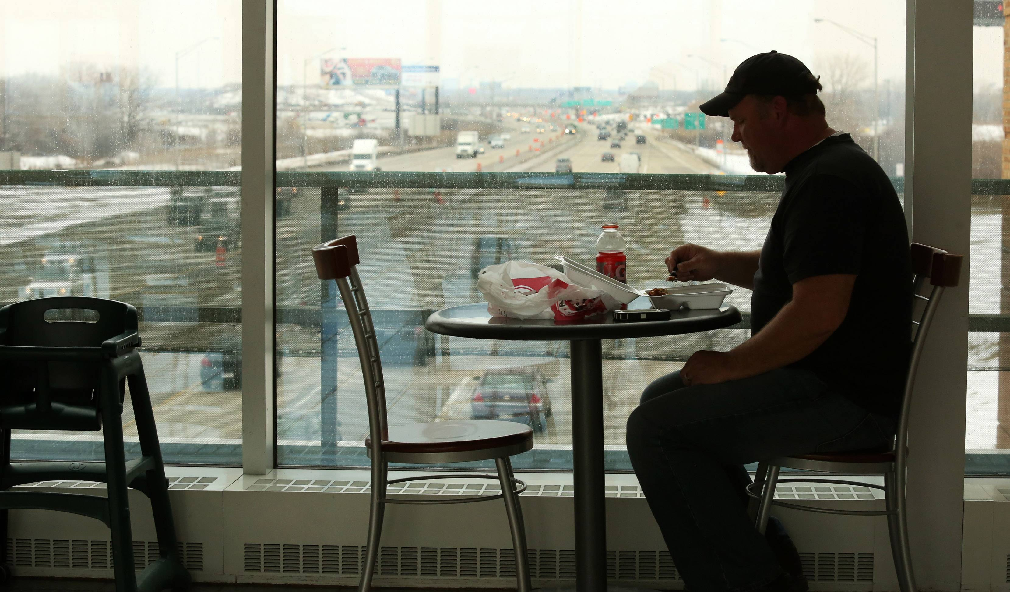 Jim Scharpf eats lunch in the Des Plaines Tollway Oasis on Thursday, March 13, 2014. View is looking west at the Jane Addams Memorial Tollway.