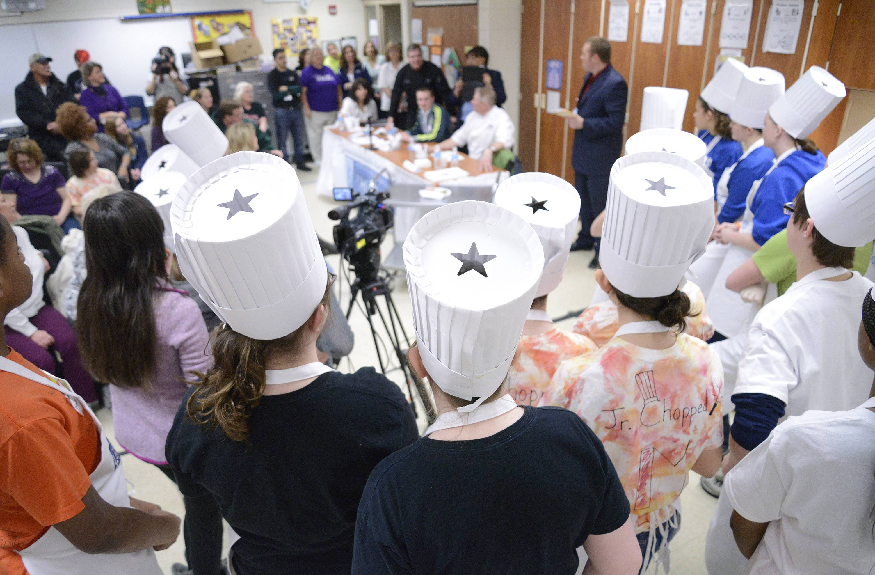 "Teams of students from seven middle schools in the Elgin School District U-46 gather around the judges to see who was eliminated from the competition after the second of four rounds in the ""Junior Chopped: A Middle School Cooking Competition"" at South Elgin High School on Saturday."