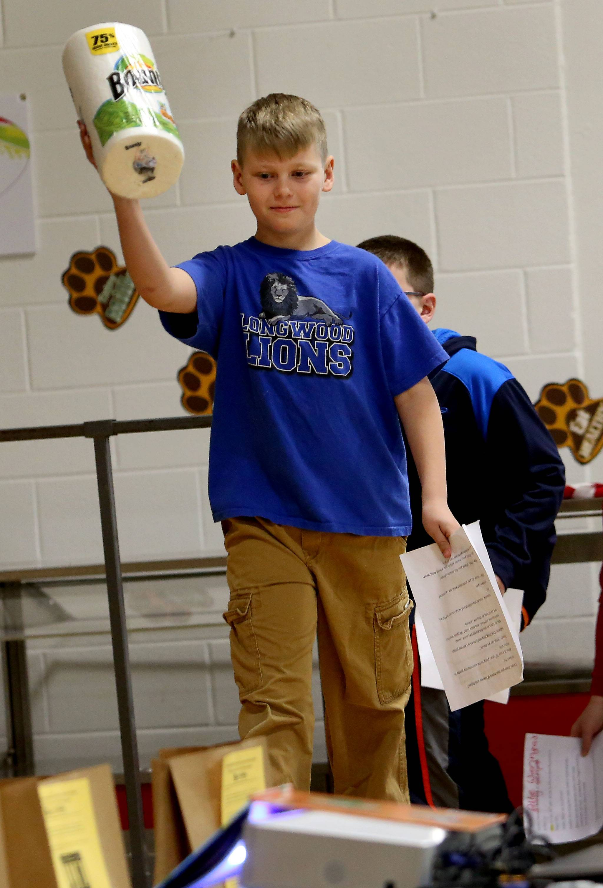 Fourth-grader Carter Burgoon, with the student council, leads the way with a pantry item as Longwood Elementary School in Naperville kicks off its 25th anniversary food drive for Loaves & Fishes Community Pantry.