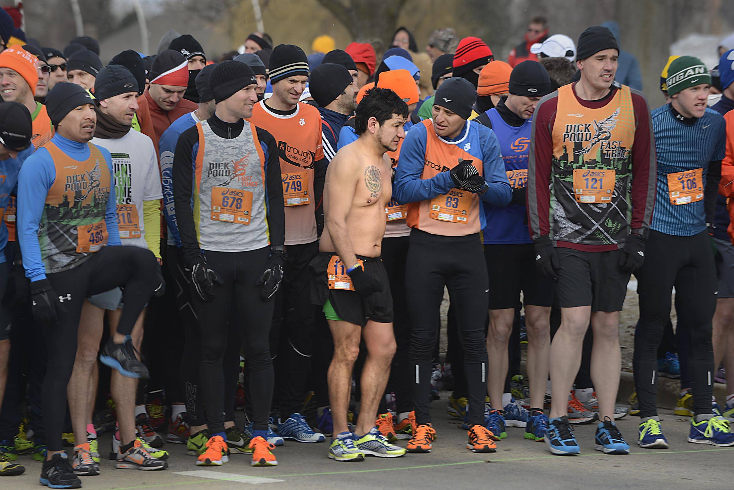 Elpidio Vilchez, of Chicago, draws attention from bundled up runners as they take the starting line, in below-zero wind chill temperatures, Sunday at the March Madness Half Marathon in Cary.