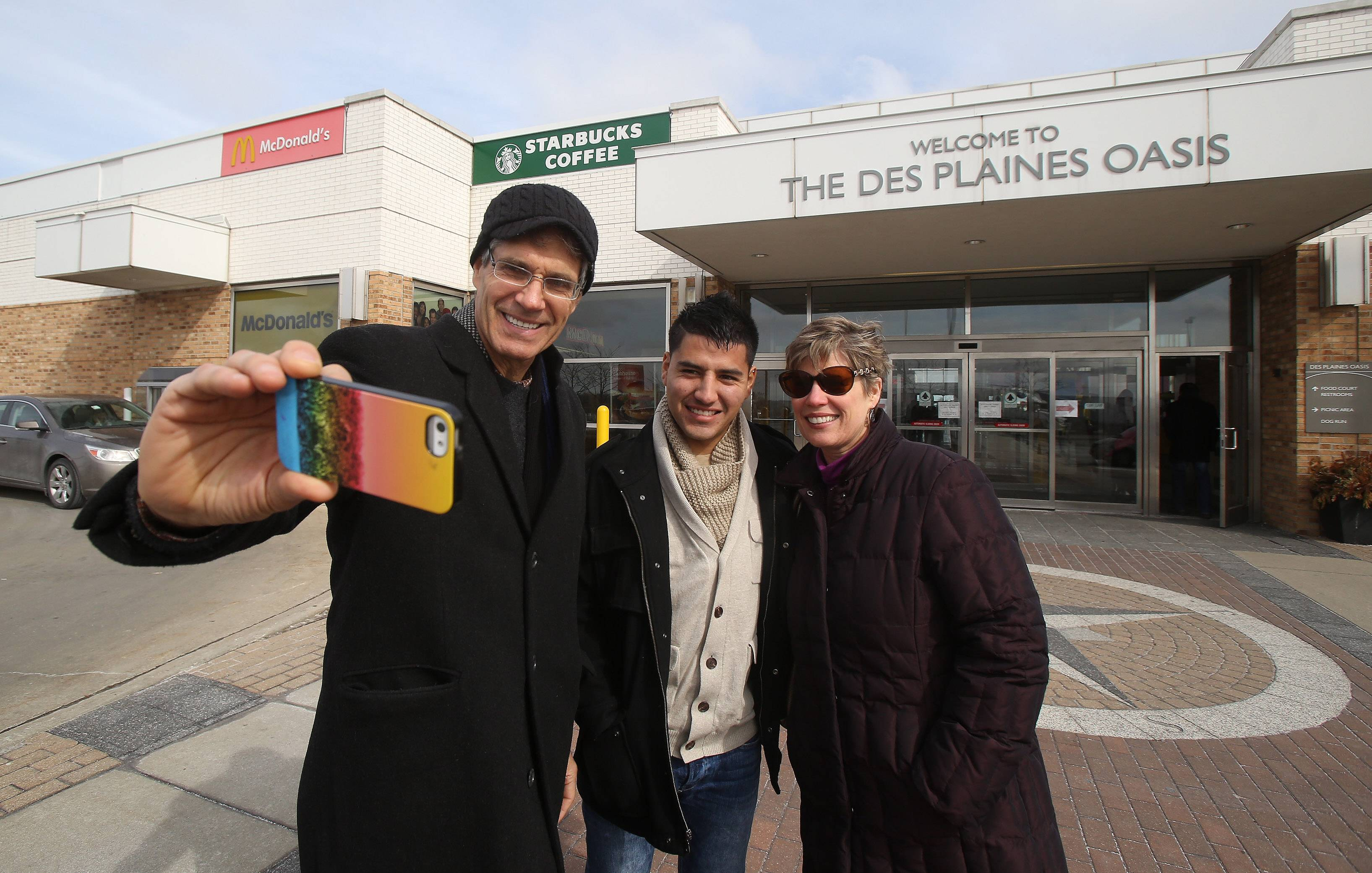 Streamwood residents Larry Pahl takes a picture of himself with Oliver Huerta and Pahl's wife, Lynn, on the last day of operation of the Des Plaines Oasis Sunday. The oasis is closing to allow for widening of the tollway to four lanes each way. The Bartlett High School civics teacher remembered visitng the Oasis during the its first year in 1959 when he was nine-years-old.