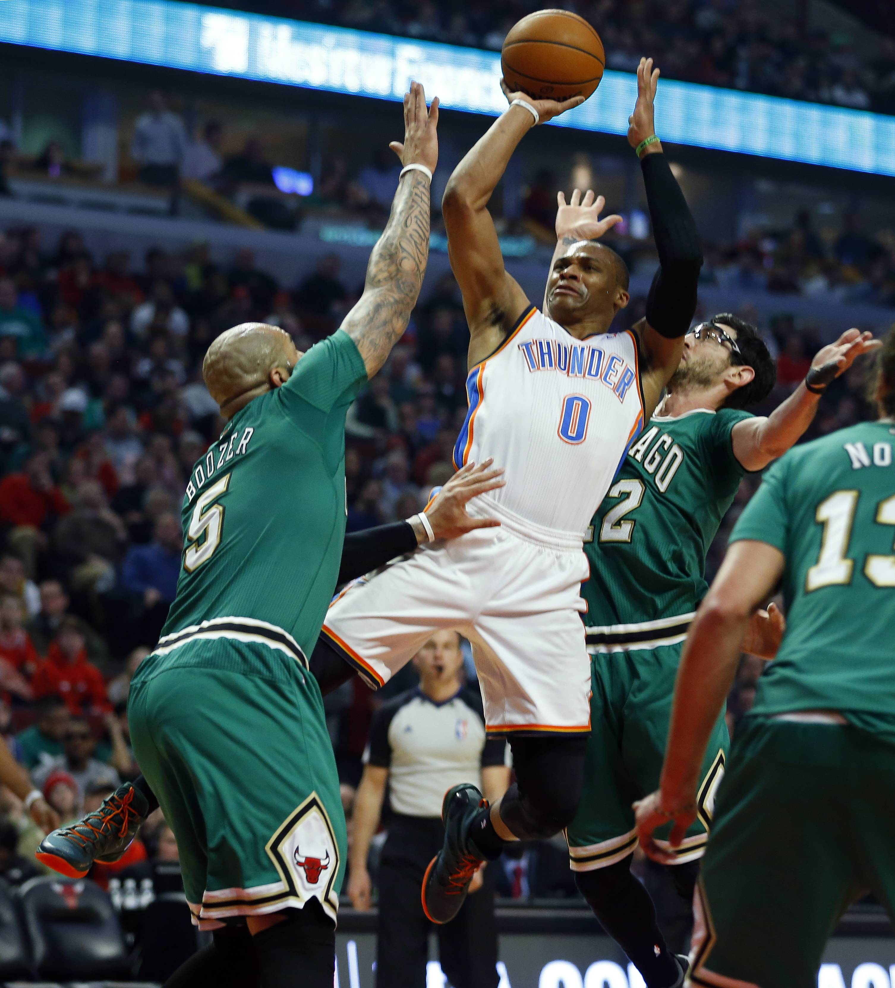 Oklahoma City guard Russell Westbrook shoots over the Bulls' Carlos Boozer and Kirk Hinrich, right, during the first half Monday night.