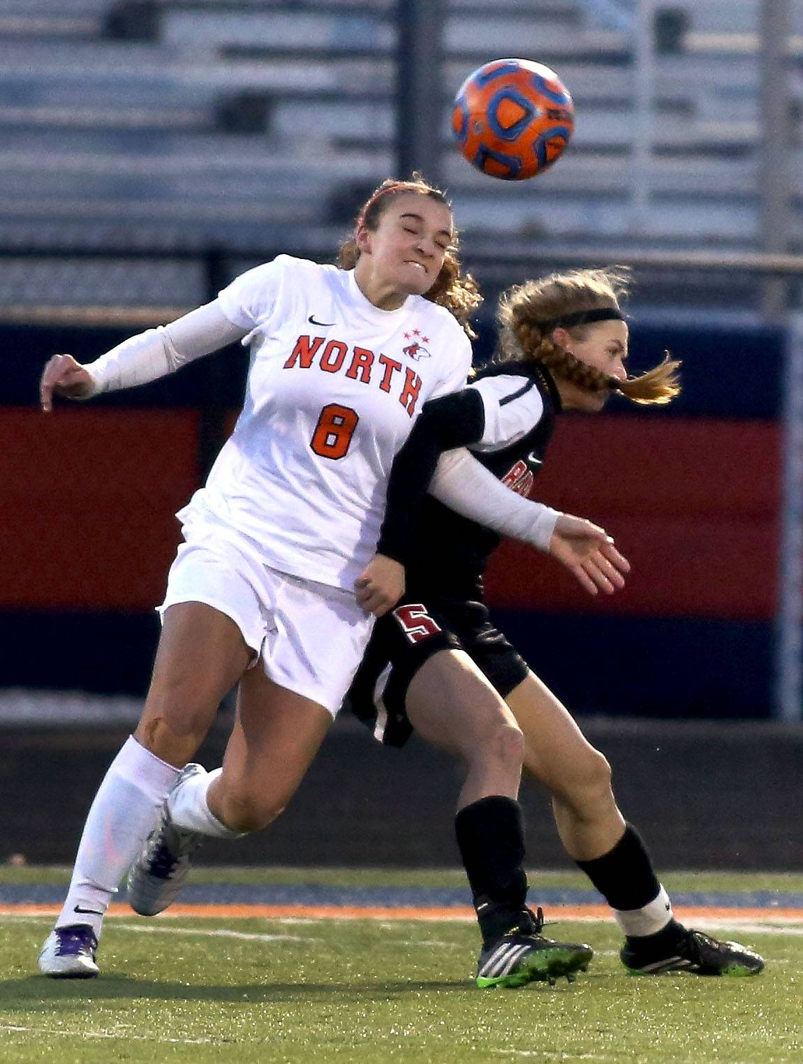 Naperville North's Abbie Boswell, left, heads the ball away from Jackie Batliner of Barrington in girls soccer action on Monday in Naperville.