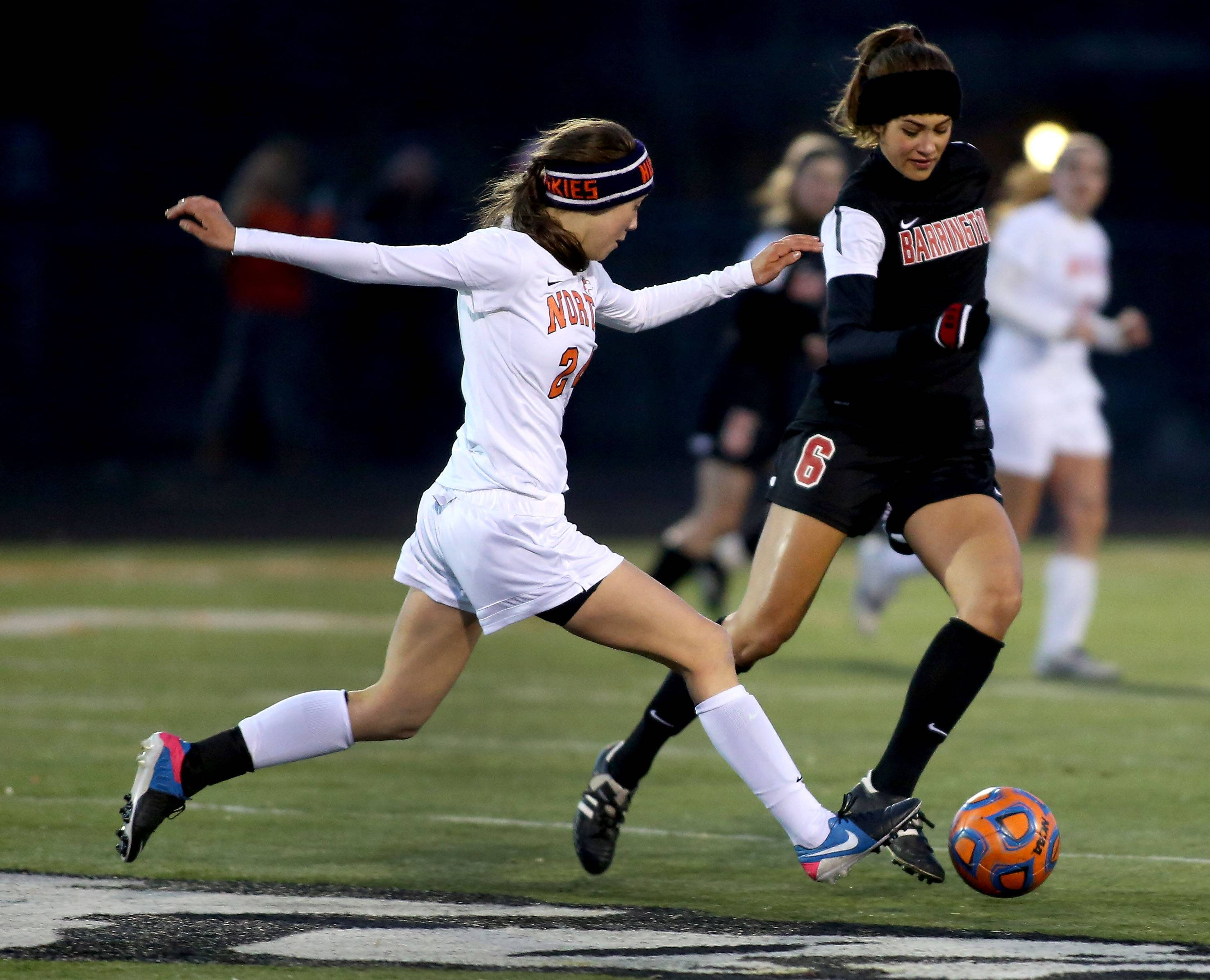 Naperville North's Allison Svoboda, left, moves in as Nicole Niro of Barrington takes control of the ball in girls soccer action on Monday in Naperville.