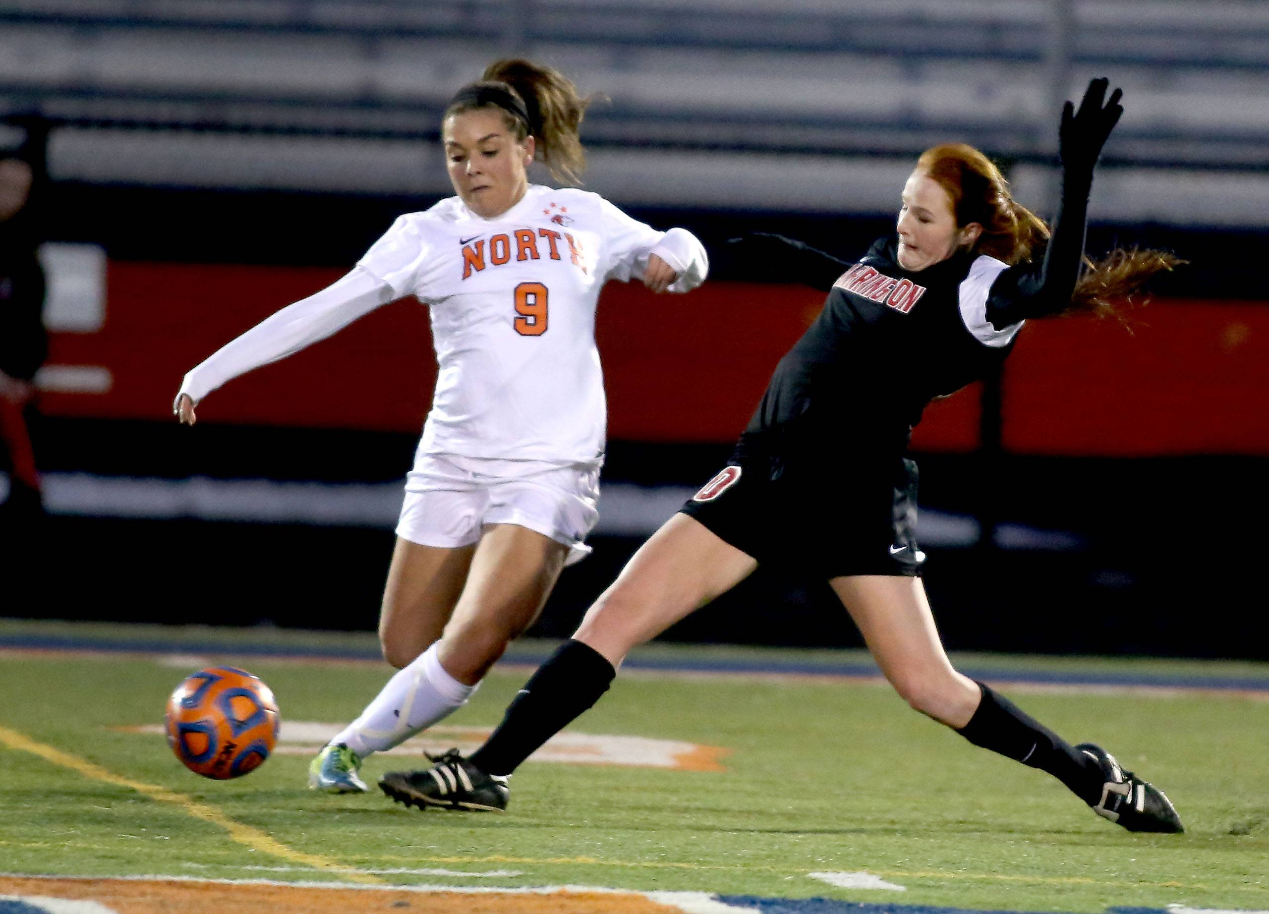 Bev Horne/bhorne@dailyherald.comNaperville North's Ashley Santos, left and Barrington's Carrie Madden, right in girls soccer action on Monday in Naperville.