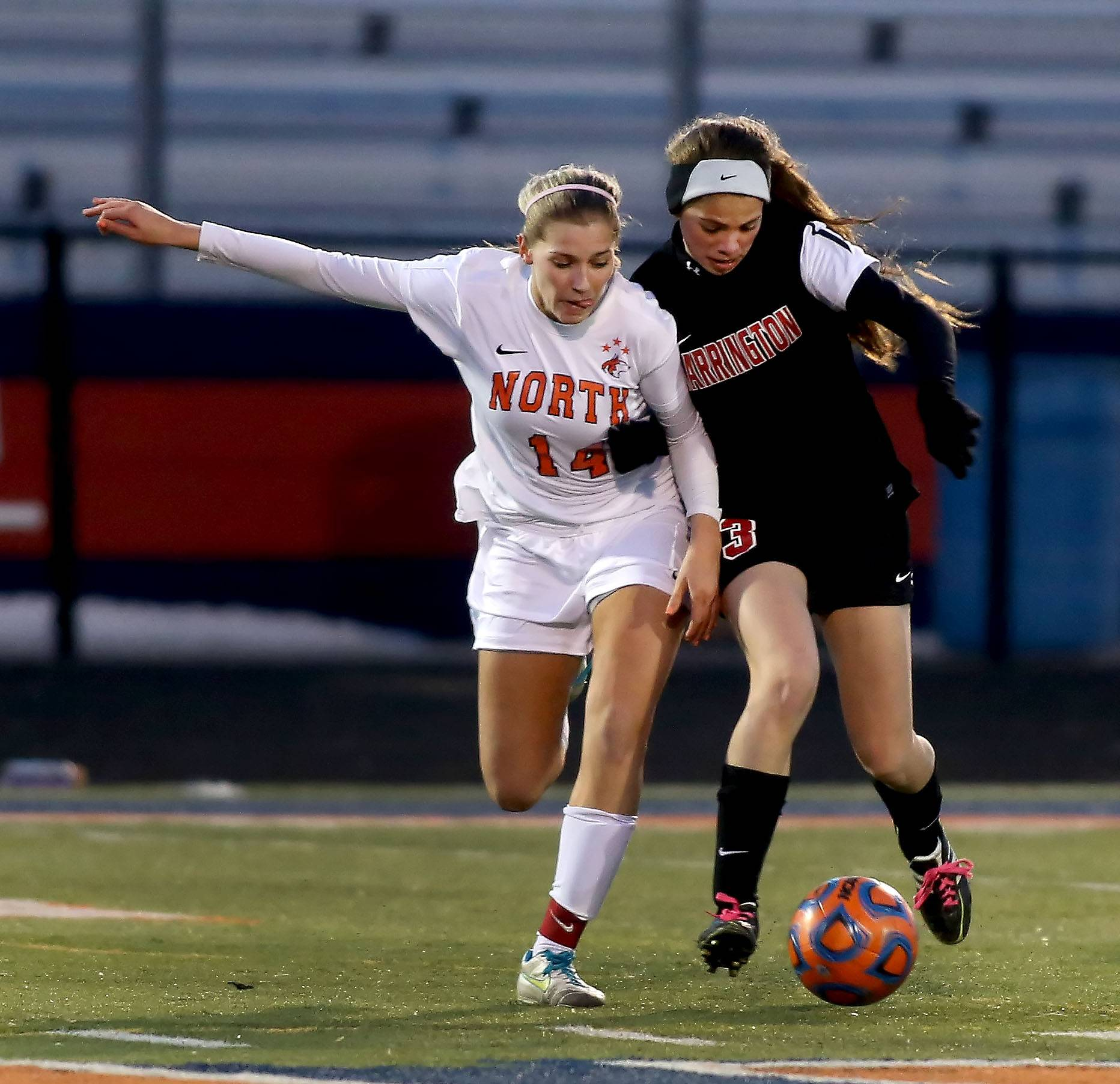 Naperville North's Olivia Stapleton, left and Barrington's Kelsey Muniz look for control of the ball in girls soccer action on Monday in Naperville.