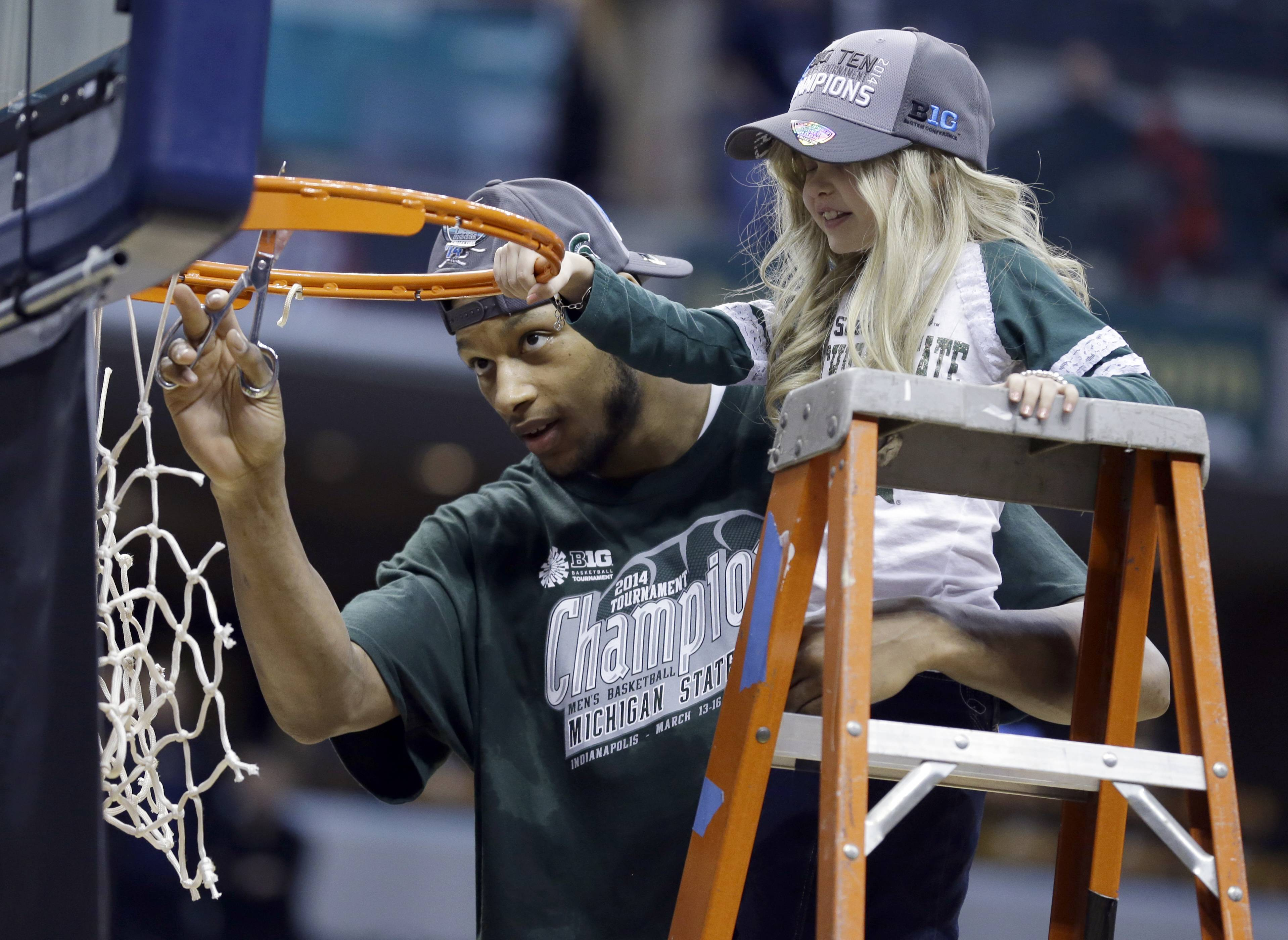 Michigan State forward Adreian Payne, left, cuts the net with Lacey Holsworth, who is battling cancer, after the Spartans defeated Michigan 69-55 in the Big Ten tournament title game Sunday in Indianapolis.