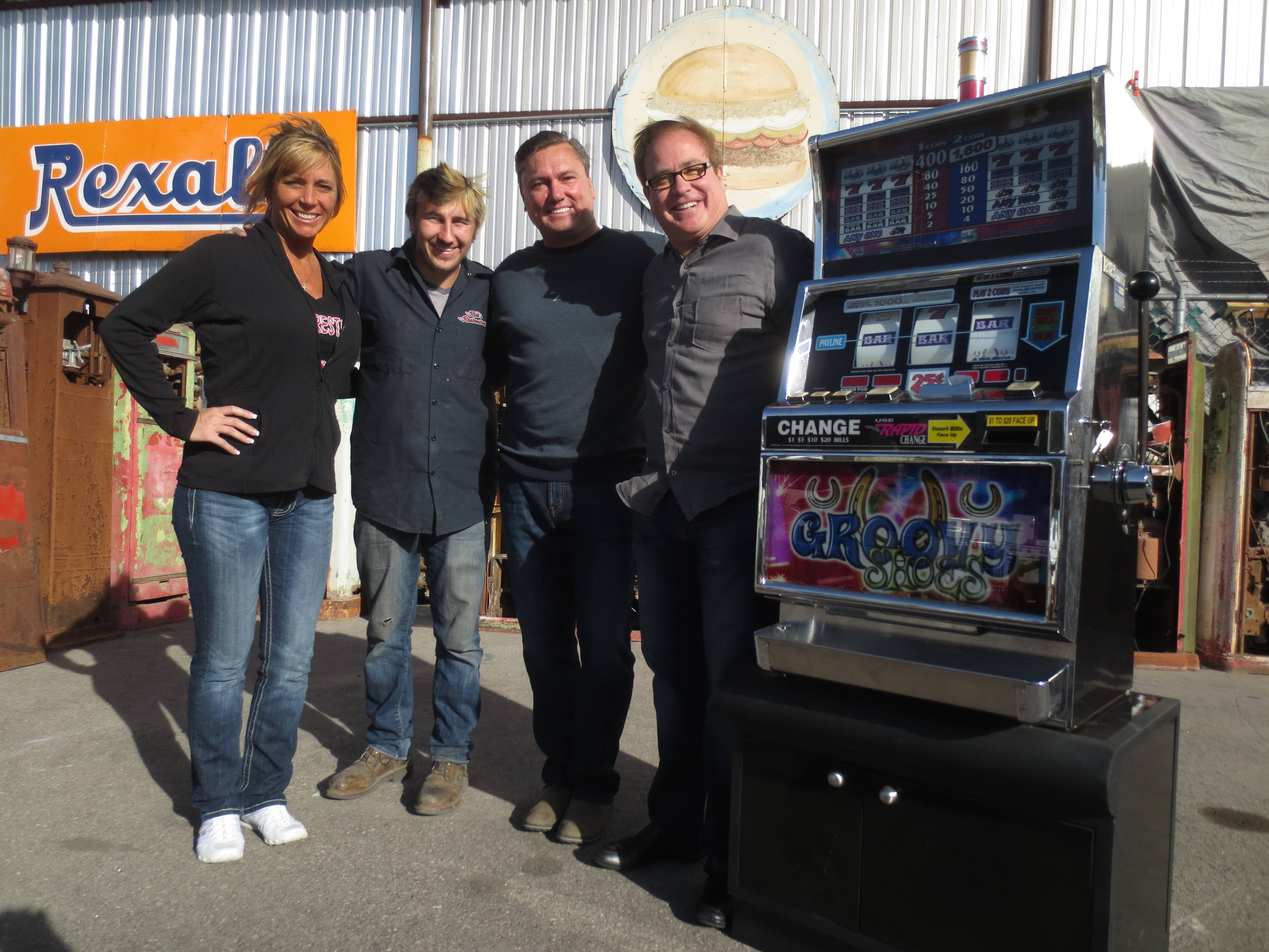 "From left, American Restoration team Kelly and Tyler Dale pose with Mark Malin and Steve Platcow of RPM Advertising beside the slot machine to be transformed into a ""Sloterator,"" a functioning slot machine that also dispenses beer."
