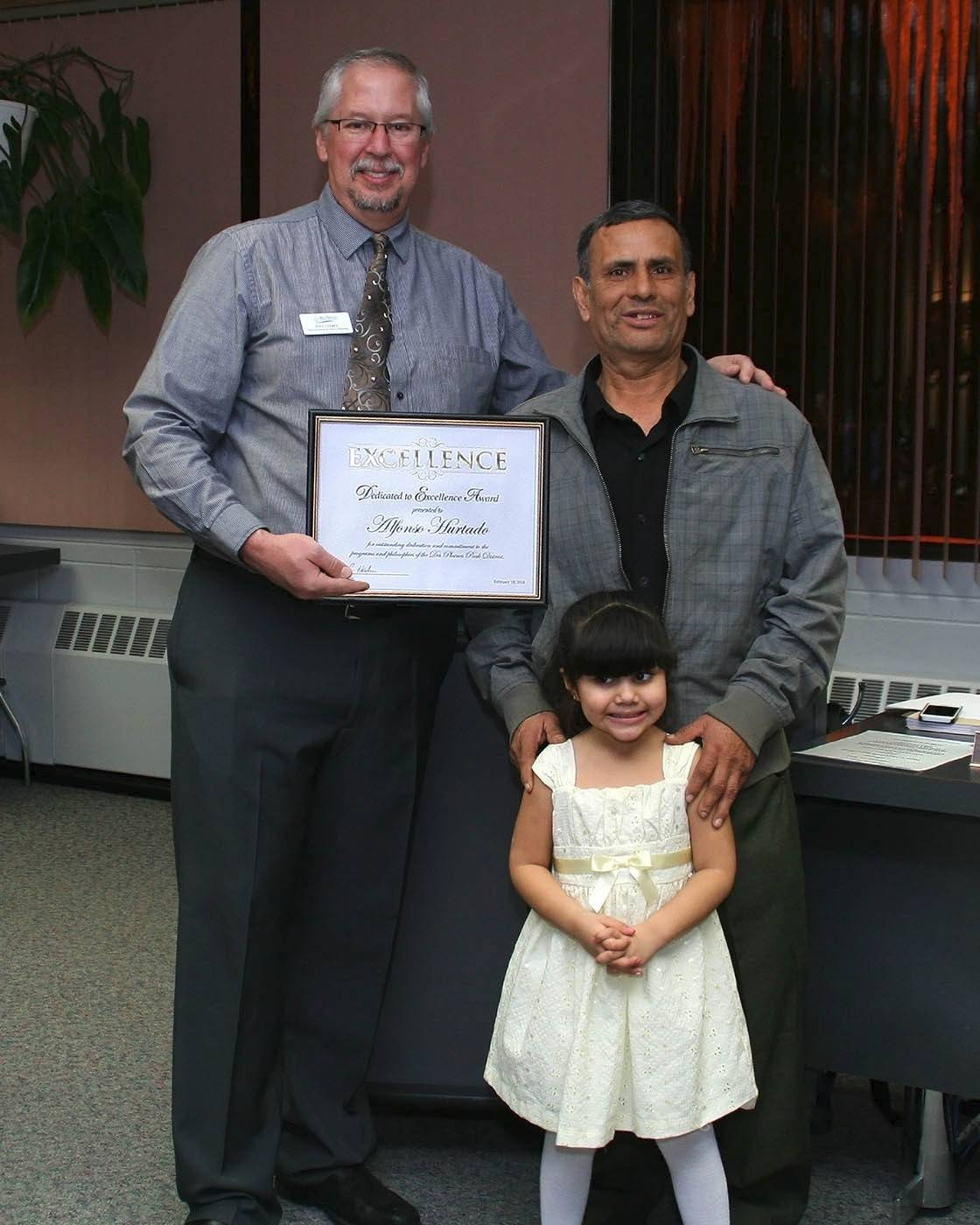 Alfonso Hurtado, along with his granddaughter, Bianca, receives his Dedicated to Excellence Award from Paul Cathey, superintendent of Parks and Planning at the park board meeting on Feb. 18.