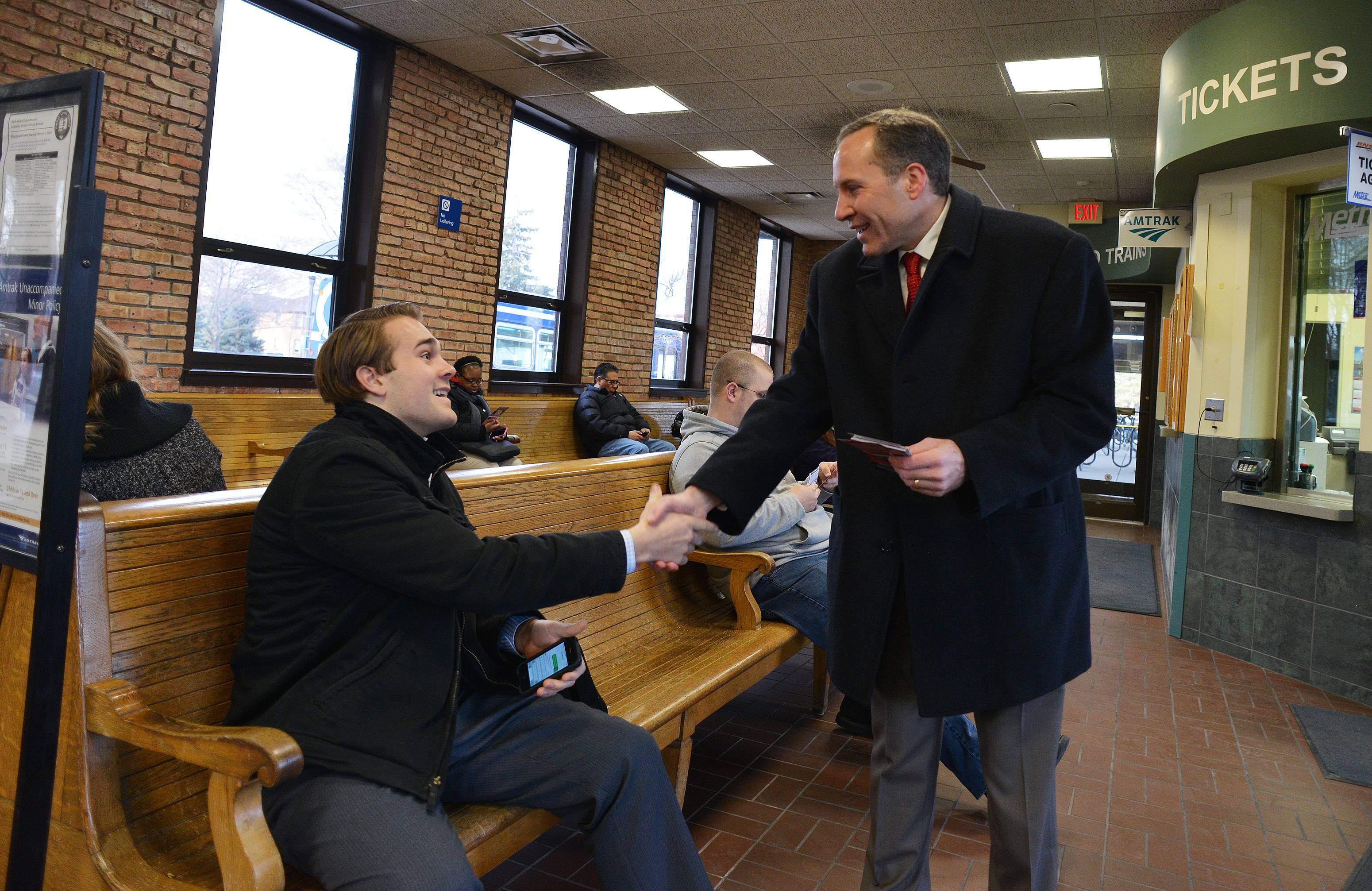 11th Congressional Candidate Chris Balkema of Channahon greets commuters, including Sam Freedlund of Naperville, early Tuesday morning at the Naperville commuter train station.