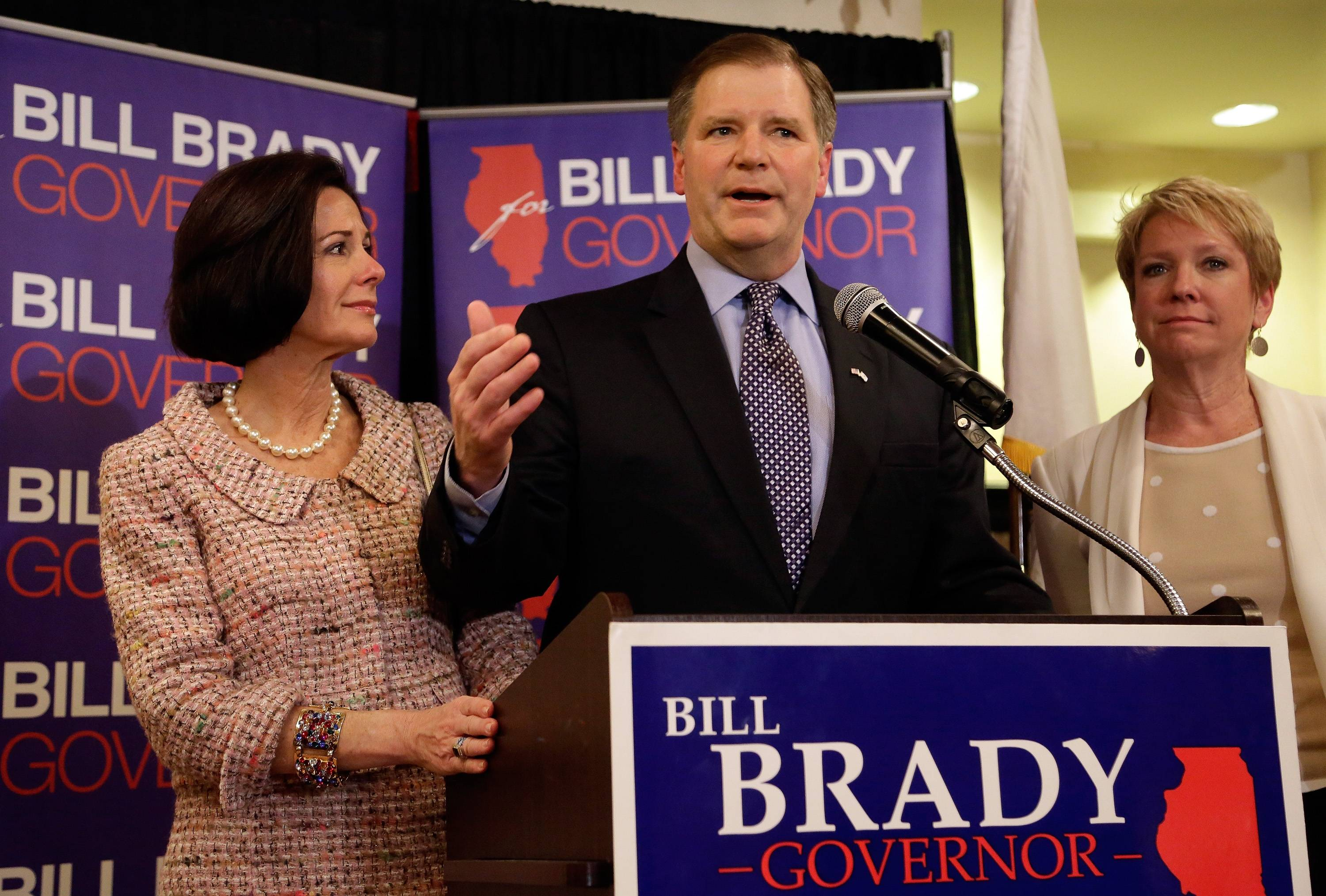 Illinois Republican gubernatorial candidate state Sen. Bill Brady, center, concedes his primary election challenge during his election night party, Tuesday, March 18, 2014, in Bloomington, Ill.  On left is Brady's wife, Nancy, and on right is Brady's running mate lieutenant governor candidate Maria Rodriguez.