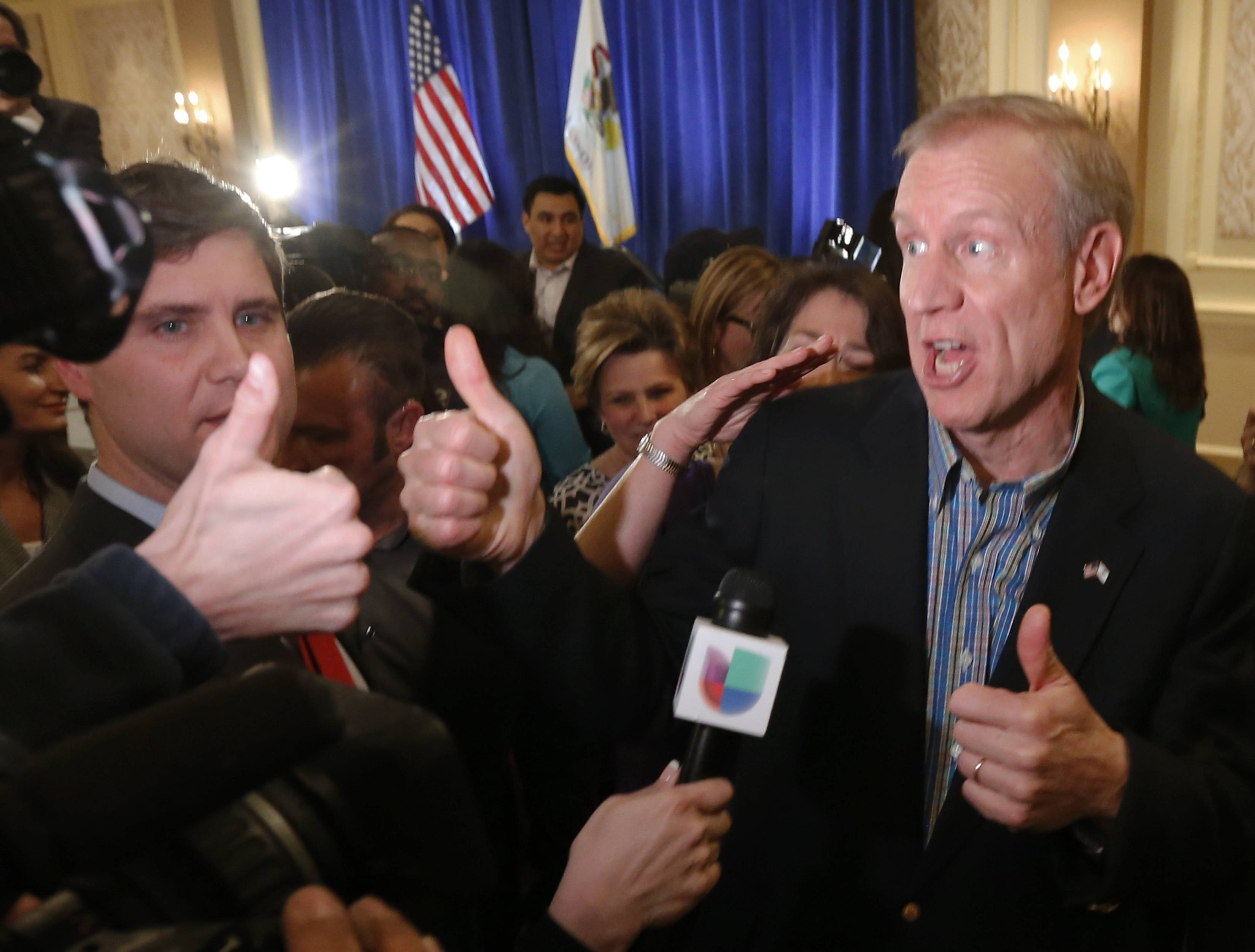Businessman Bruce Rauner, left, and his wife Diana, right, celebrate with supporters Rauner becoming the Republican gubernatorial candidate.