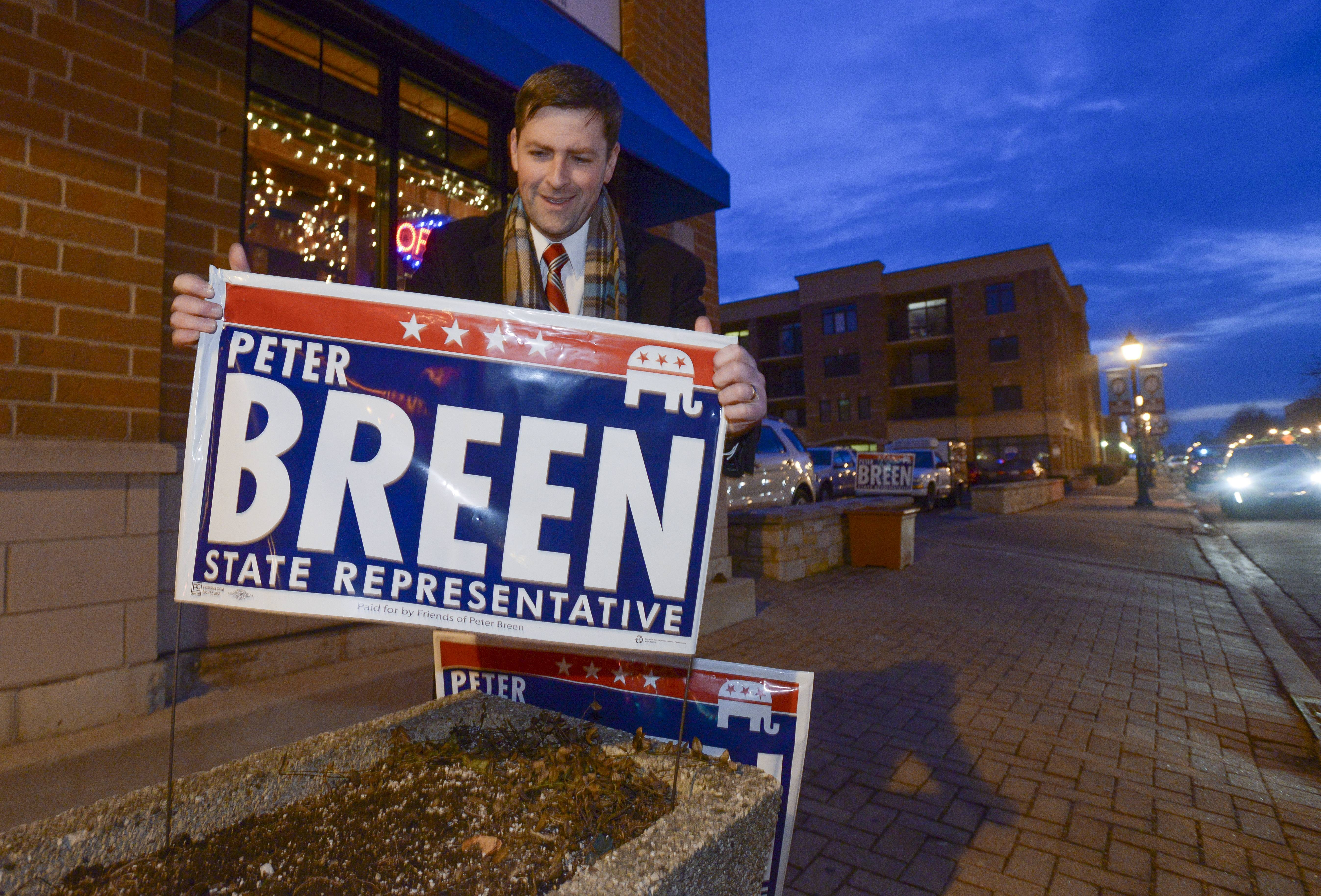 Peter Breen posts campaign signs outside Capone's restaurant in Lombard Tuesday, where his Election Night party was located. Breen took the Republican nomination in the 48th House district, ousting longtime Rep. Sandra Pihos from her seat, according to unofficial election results.