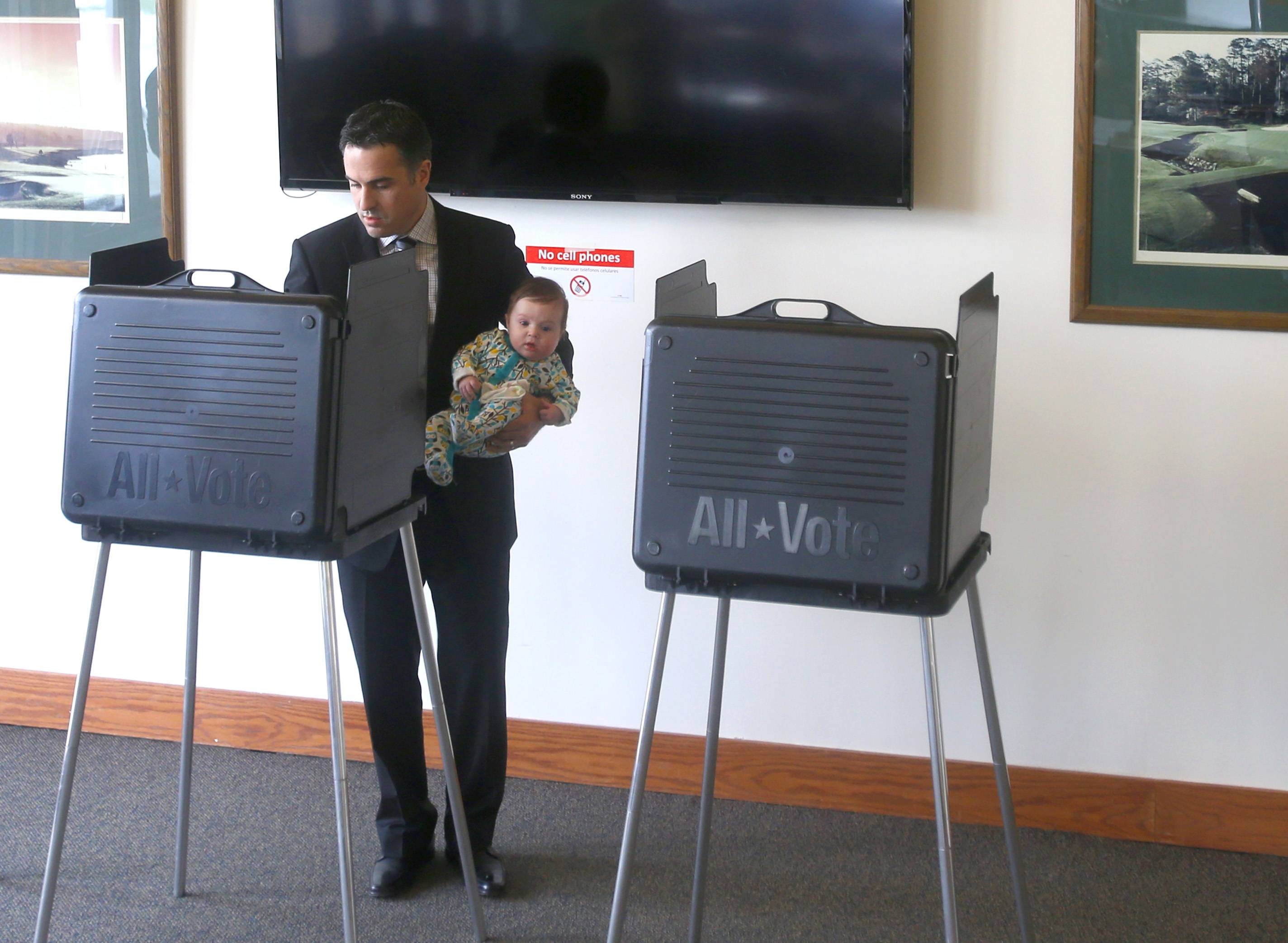 Joe Cantore, shown voting Tuesday at the Oak Brook Golf Club while holding son Joe, became the Republican nominee for president of the DuPage County Forest Preserve District by defeating Mary Lou Wehli in the GOP primary.