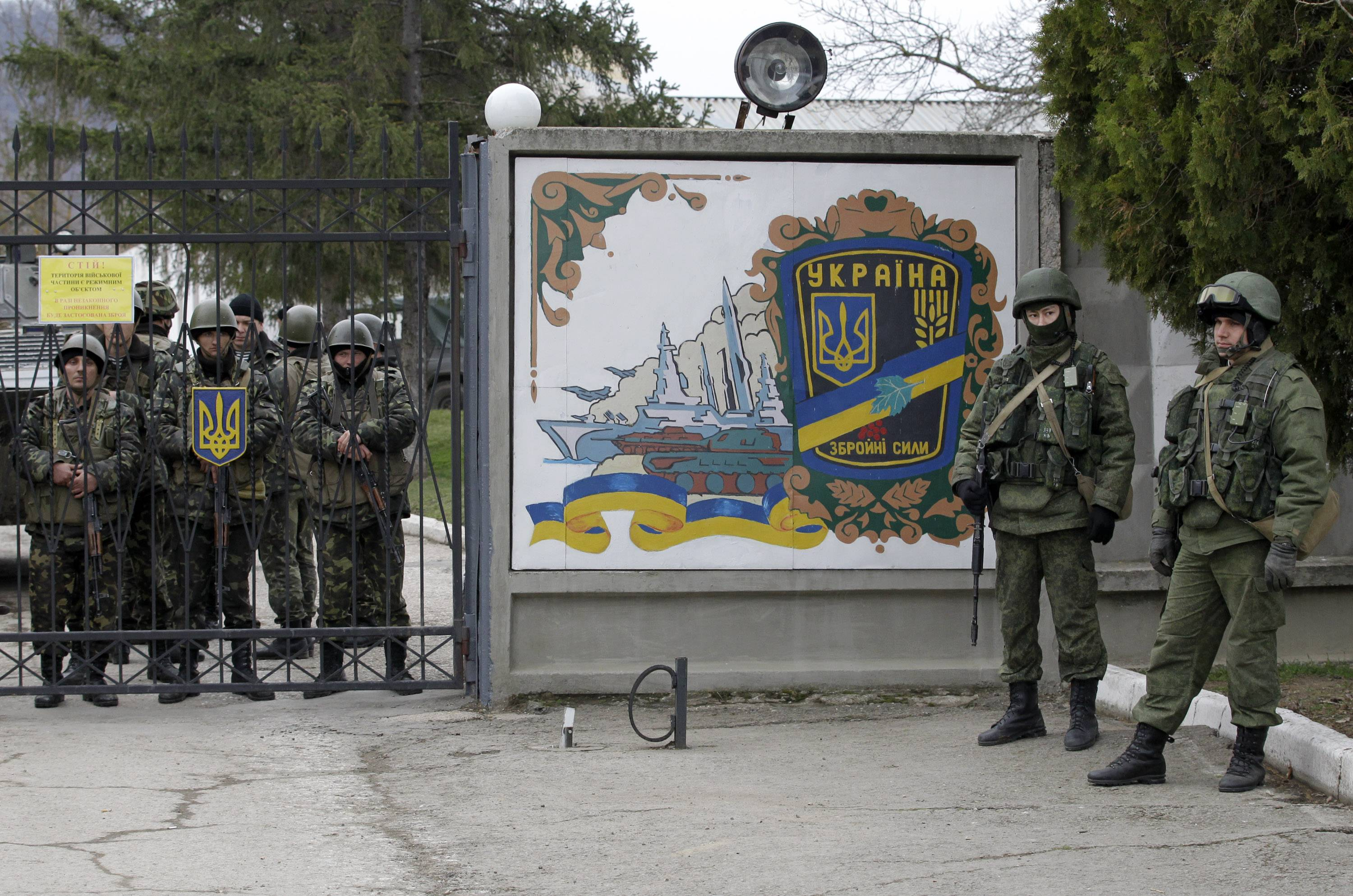 Ukrainian soldiers, left and unidentified gunmen, right, guard the gate of an infantry base in Privolnoye, Ukraine, March 2. Beyond the prize of the Black Sea peninsula of Crimea, a picture is emerging of what Russian President Vladimir Putin ultimately wants from his power play: Broad autonomy for Ukraine's Russian-speaking regions and guarantees that Ukraine will never realize the Kremlin's worst nightmare -- joining NATO.