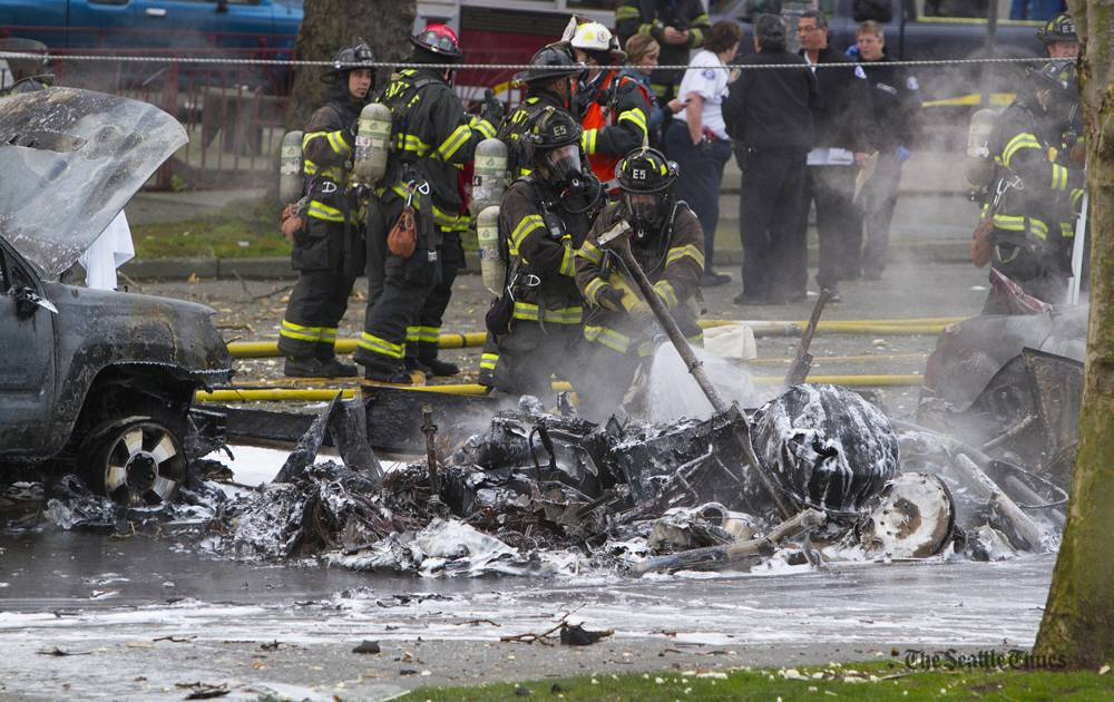 Seattle firefighters spray water on a helicopter crash outside KOMO-TV studios in Seattle on Tuesday, March 18, 2014. A KOMO-TV helicopter crashed into a city street near Seattle's Space Needle, killing two people and critically injuring a person in a car on the ground.