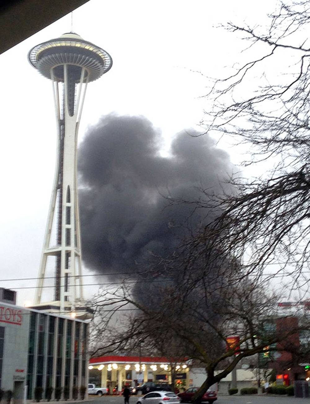 Smoke rises at the scene of a helicopter crash outside the KOMO-TV studios near the space needle in Seattle on Tuesday, March 18, 2014. The station says the helicopter was apparently coming in for a landing on its rooftop Tuesday morning when it possibly hit the side of the building and went down, hitting several vehicles on Broad Street.