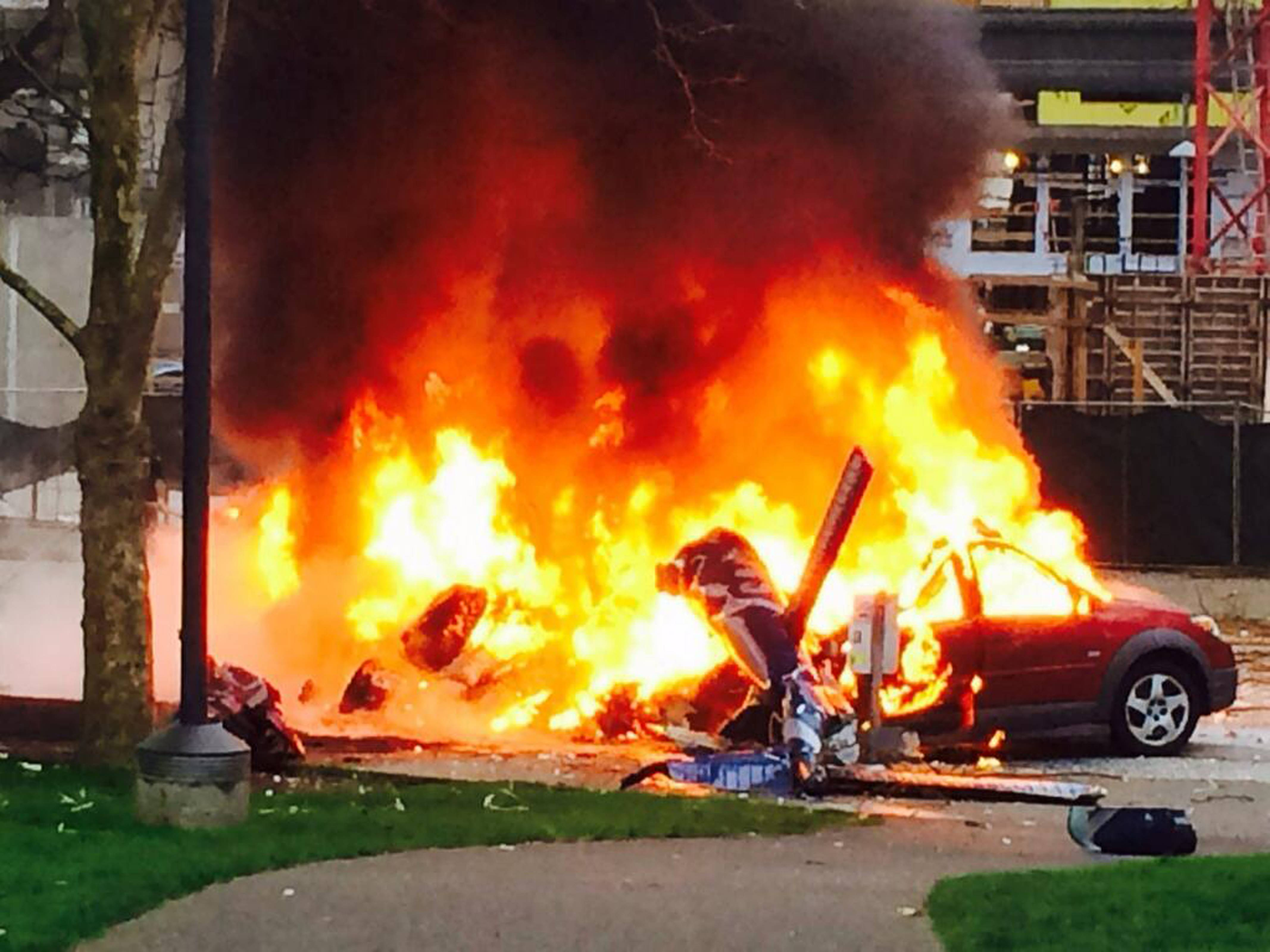 A car burns at the scene of a helicopter crash outside the KOMO-TV studios near the space needle in Seattle on Tuesday, March 18, 2014.