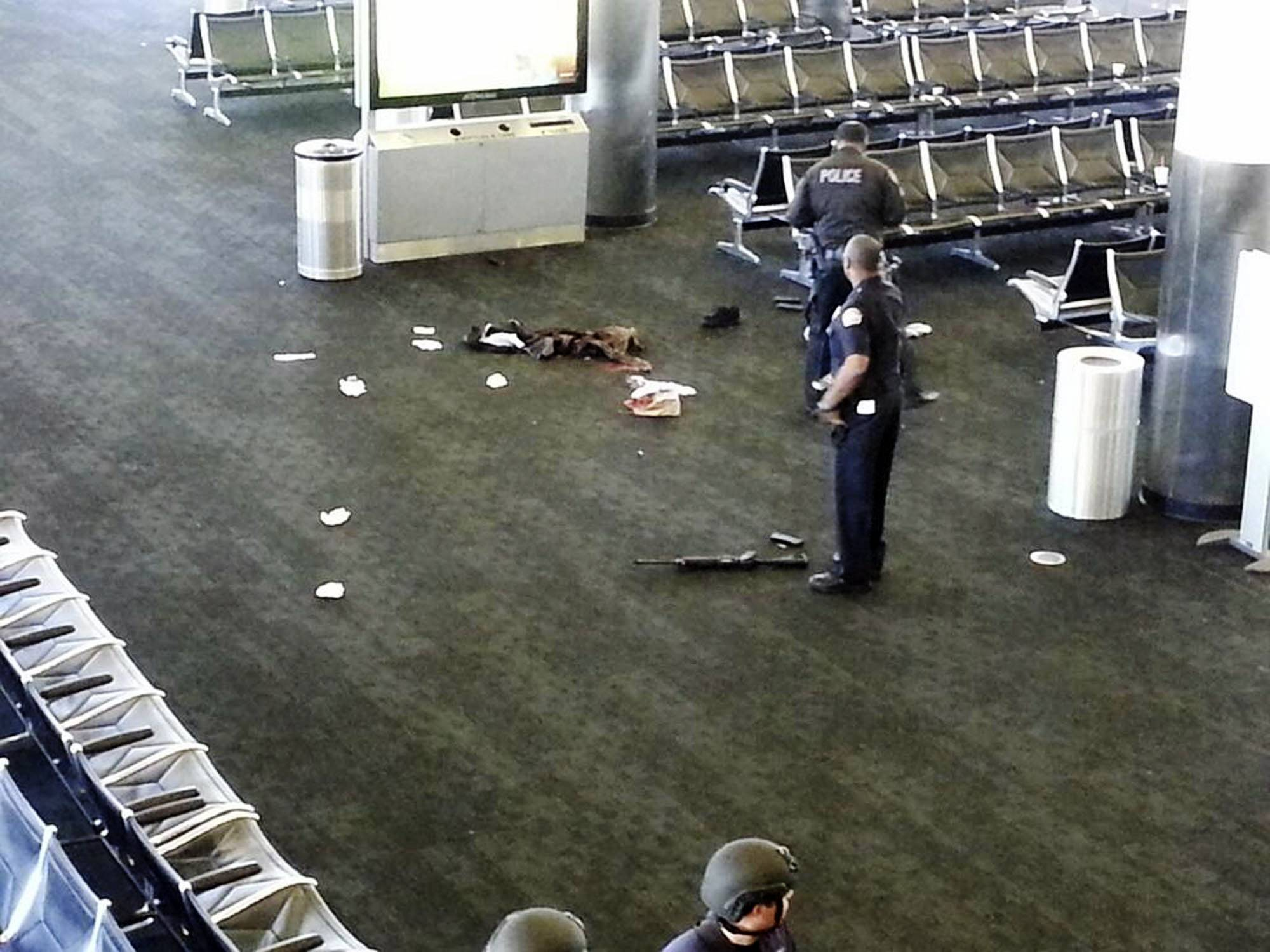 FILE - In this Nov. 1, 2013 file photo provided to the AP, which has been authenticated based on its contents and other AP reporting, police officers stand near a weapon at the Los Angeles International Airport after a gunman opened fire in the terminal, killing one person and wounding several others. A report on the emergency response to the shooting cites serious shortcomings in communication between agencies that left major commanders in the dark and a long lag in establishing a coordinated response.