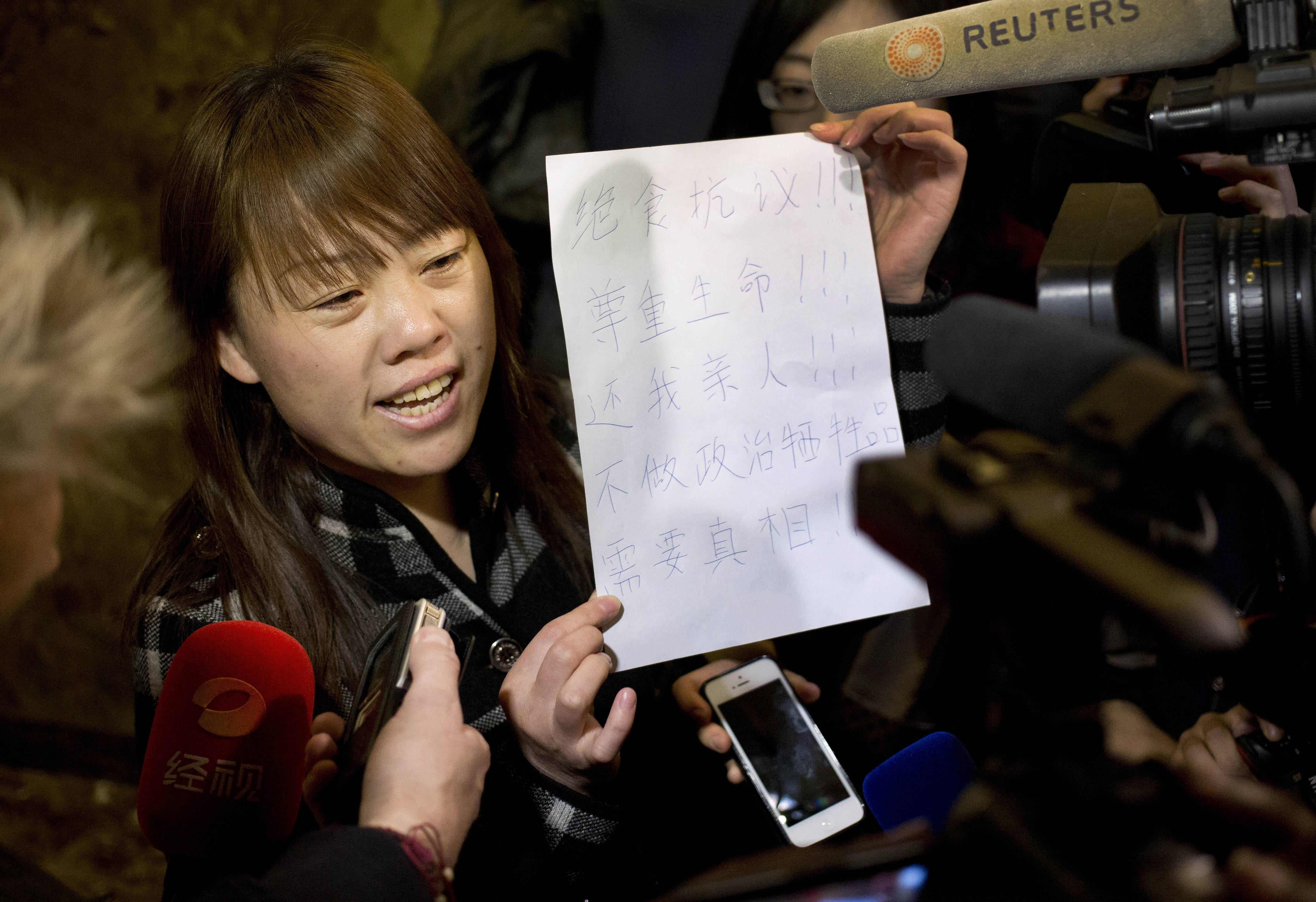 "A relative of a Chinese passenger aboard the missing Malaysia Airlines Flight MH370 shows a paper reading ""Hunger strike protest, Respect life, Return my relative, Don't want become victim of politics, Tell the truth"" as she speaks to the media outside a hotel ballroom after attending a briefing held by airlines' officials in Beijing, China, Tuesday. Families of the passengers aboard the missing plane decided to organize a hunger strike to express their anger and disappointment at the handling of the situation by authorities."
