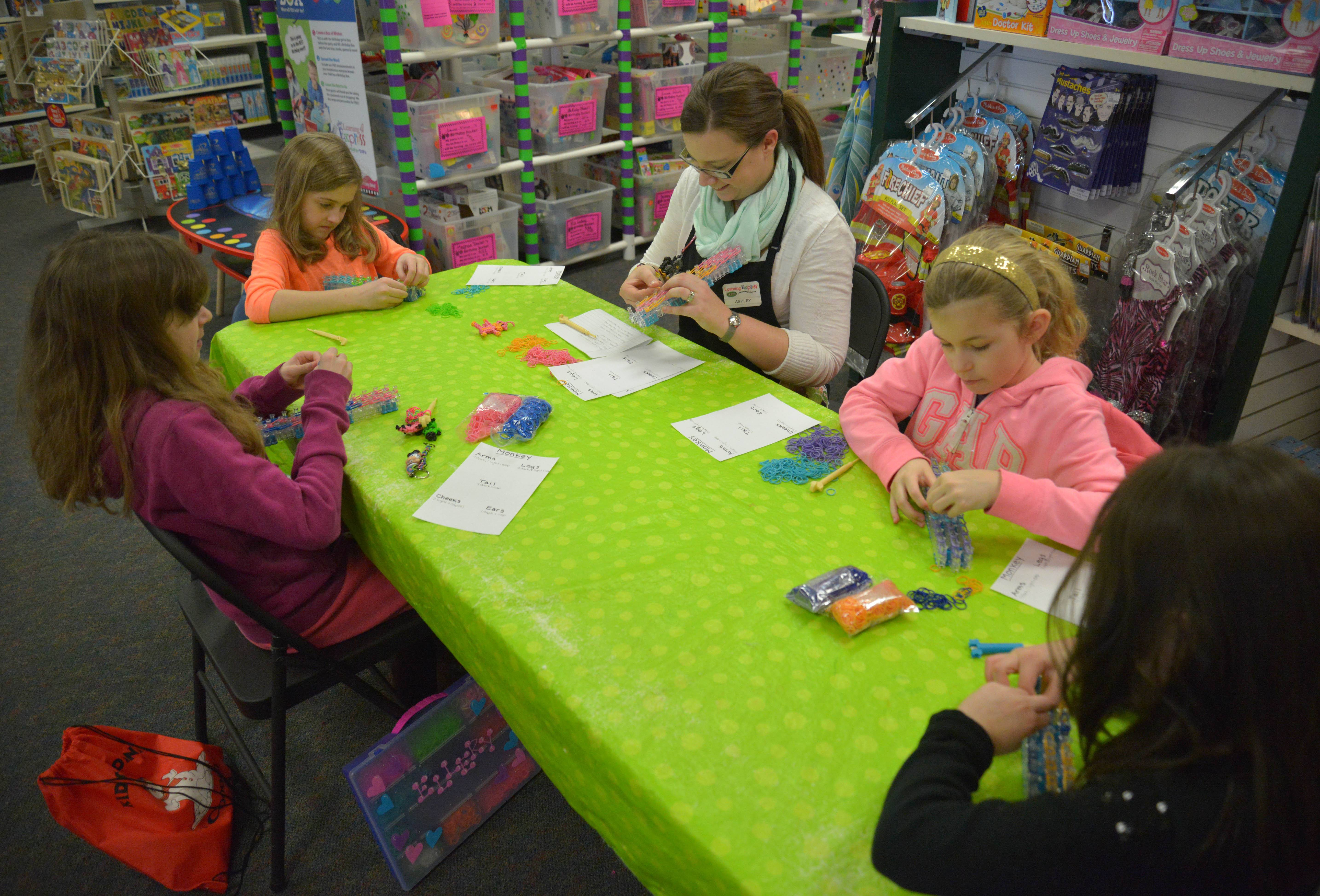The Learning Express toy store bustles with shoppers, but Ellery Patterson, 11, of Aurora, Kaeli Wloch, 10, of Romeoville, instructor Ashley Humberstone, of Lombard, Hailey Mitchell, 8, of Aurora, and Eleanor Cuasay, 8, of Naperville, focus on turning rubber bands into a colorful Rainbow Loom monkeys.
