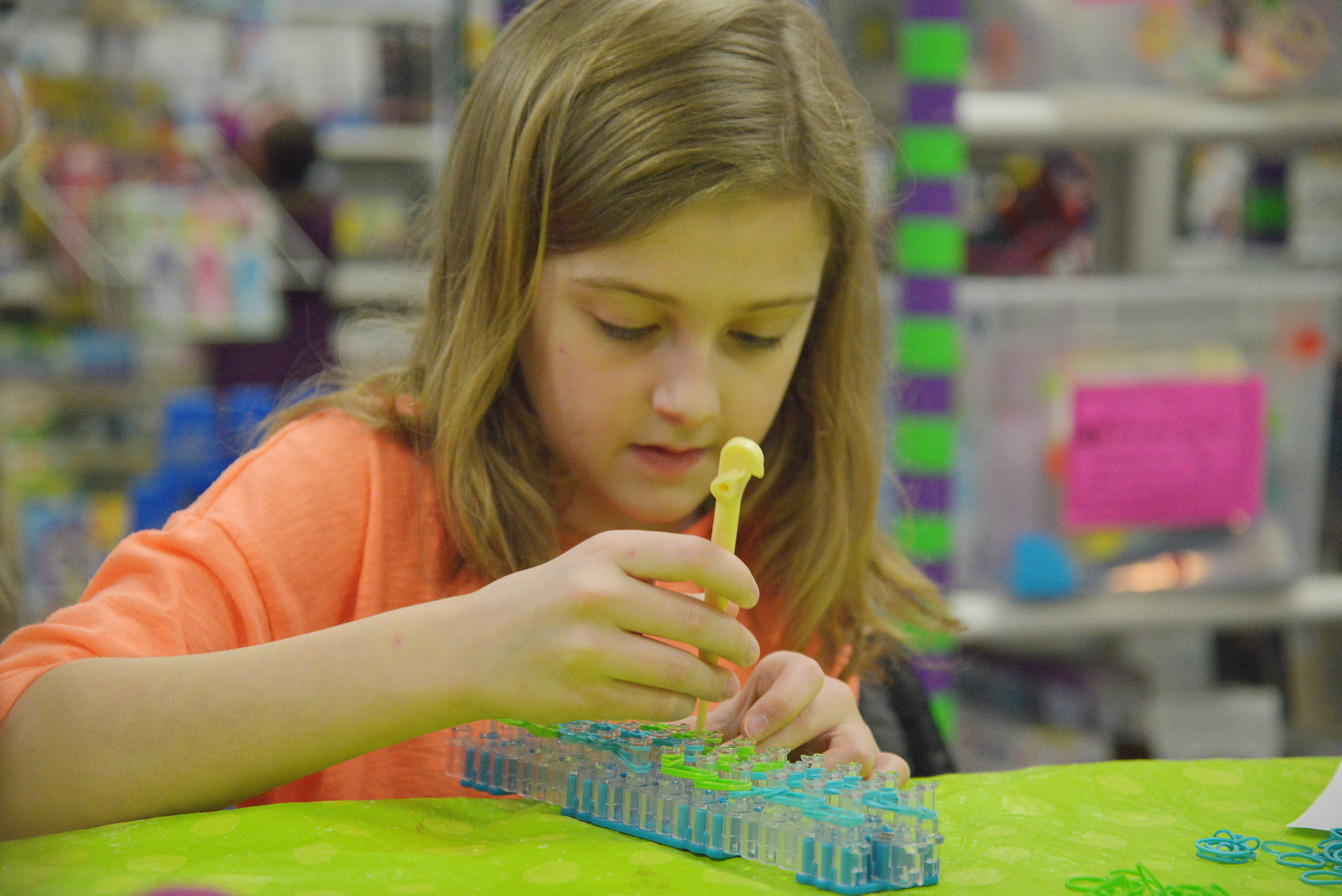 Using a hook to wrap a small rubber band around a peg on her Rainbow Loom kit, Kaeli Wloch, 10, of Romeoville, makes a colorful monkey at the Learning Express toy store in Naperville.