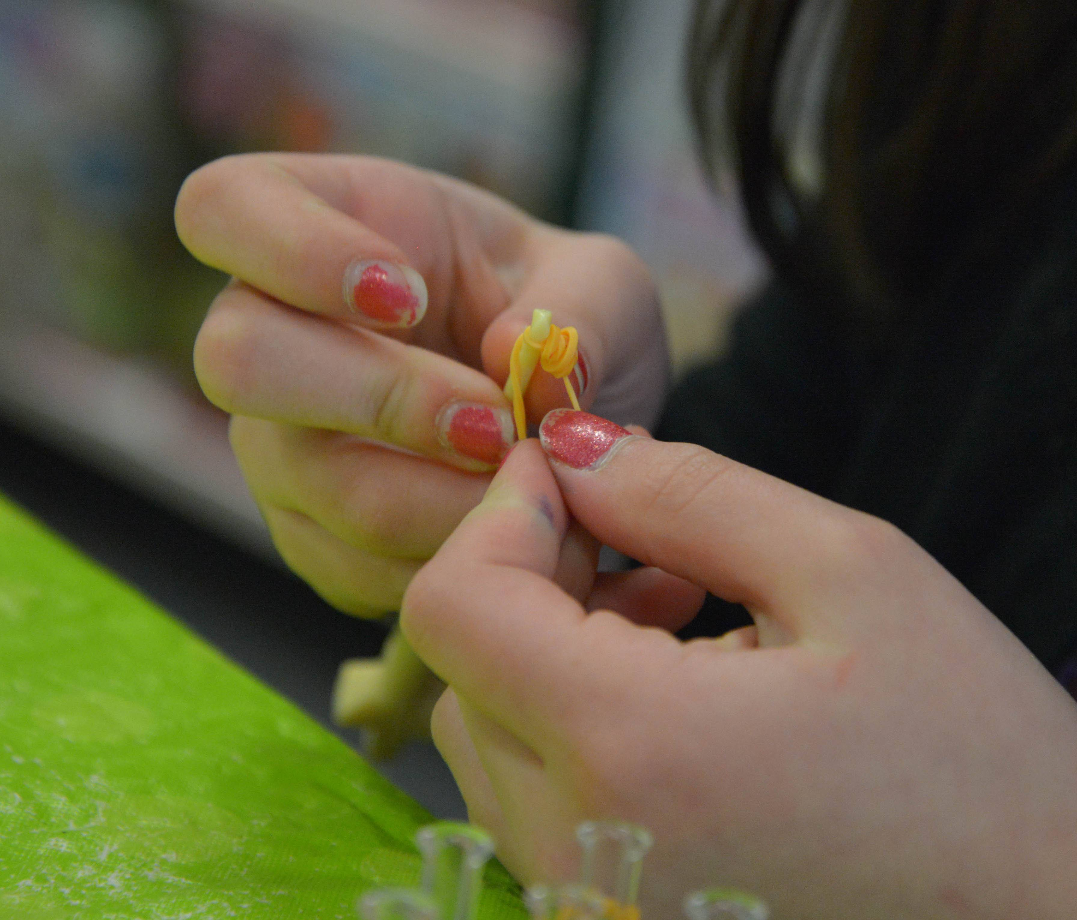 The hands of Ellery Patterson, 11, of Aurora, are hard at work on her Rainbow Loom monkey during a class at the Learning Express toy store in Naperville.