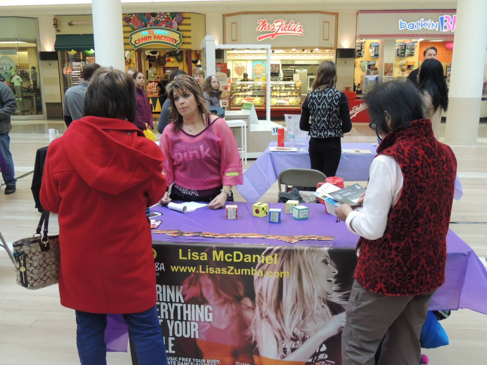 One of the exhibiters at the Fitness February Fair was Zumba Instructor Lisa McDaniel who also volunteers as Secretary for the Healthy Lombard Foundation. Here she is shown sharing information with visitors to the Healthy Lombard 2014 Fitness February Fair that was held in the Center Court of the Yorktown Center Mall. Jay Wojcik