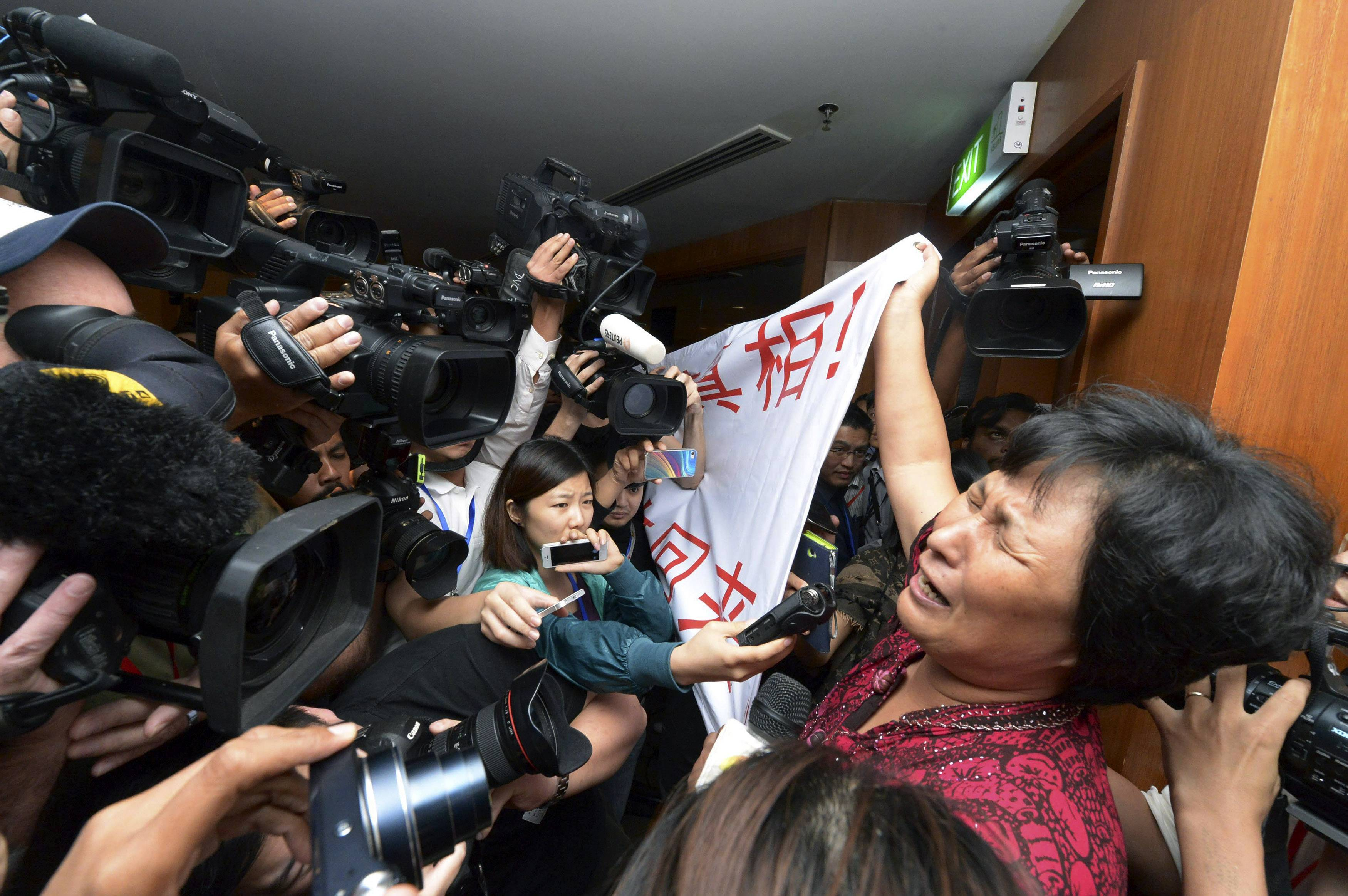"A Chinese relative of passengers aboard a missing Malaysia Airlines plane cries as she holds a banner in front of journalists reading ""We are against the Malaysian government for hiding the truth and delaying the rescue. Release our families unconditionally!"" at a hotel in Sepang, Malaysia, Wednesday, March 19, 2014."