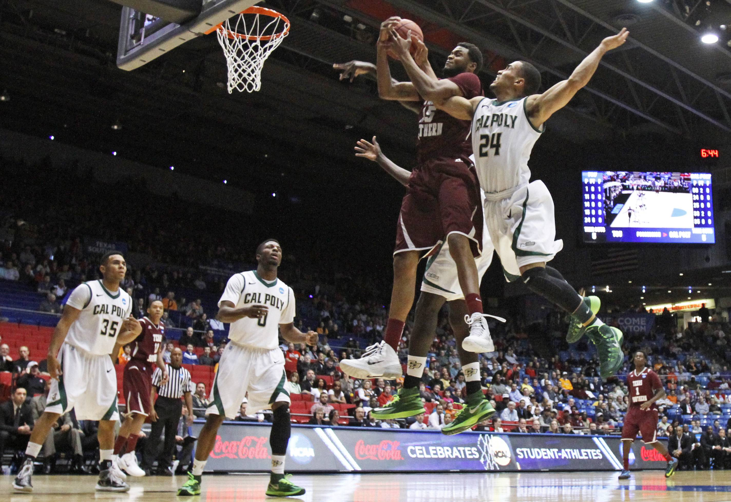 Texas Southern forward D'Angelo Scott (15) goes up for a rebound against Cal Poly guard Jamal Johnson (24) in the first half of a first-round game of the NCAA college basketball tournament on Wednesday in Dayton, Ohio.