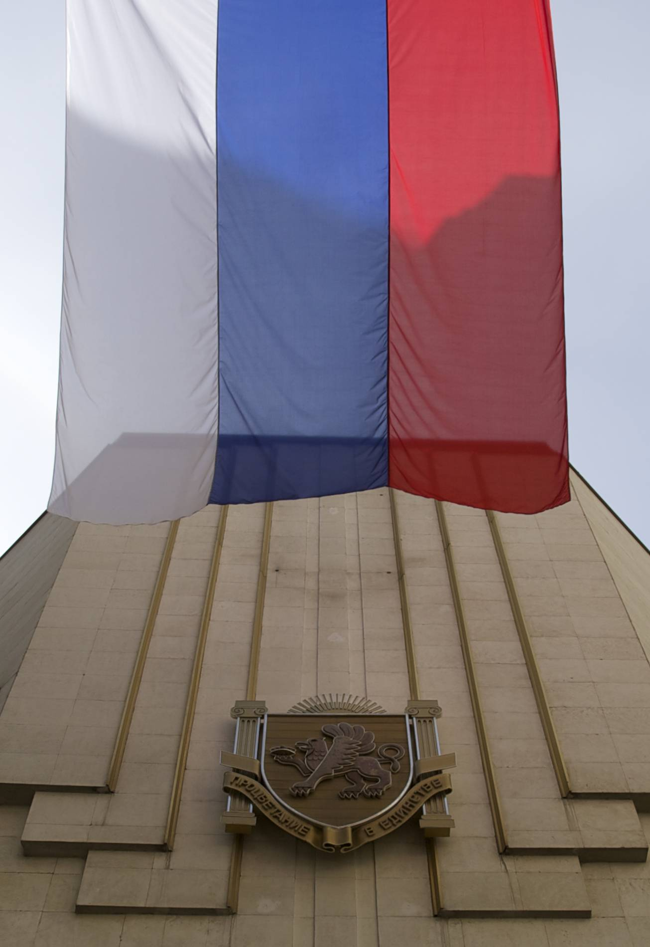 "Russian flag waves next to a local parliament building bearing the Crimea regional emblem, as workers install a new sign on the building, reading ""State council of Crimean Republic"", in Simferopol, Crimea, on Wednesday, March 19, 2014. Russian parliament is due to approve Crimean appeal to join the Russia Federation on Thursday."