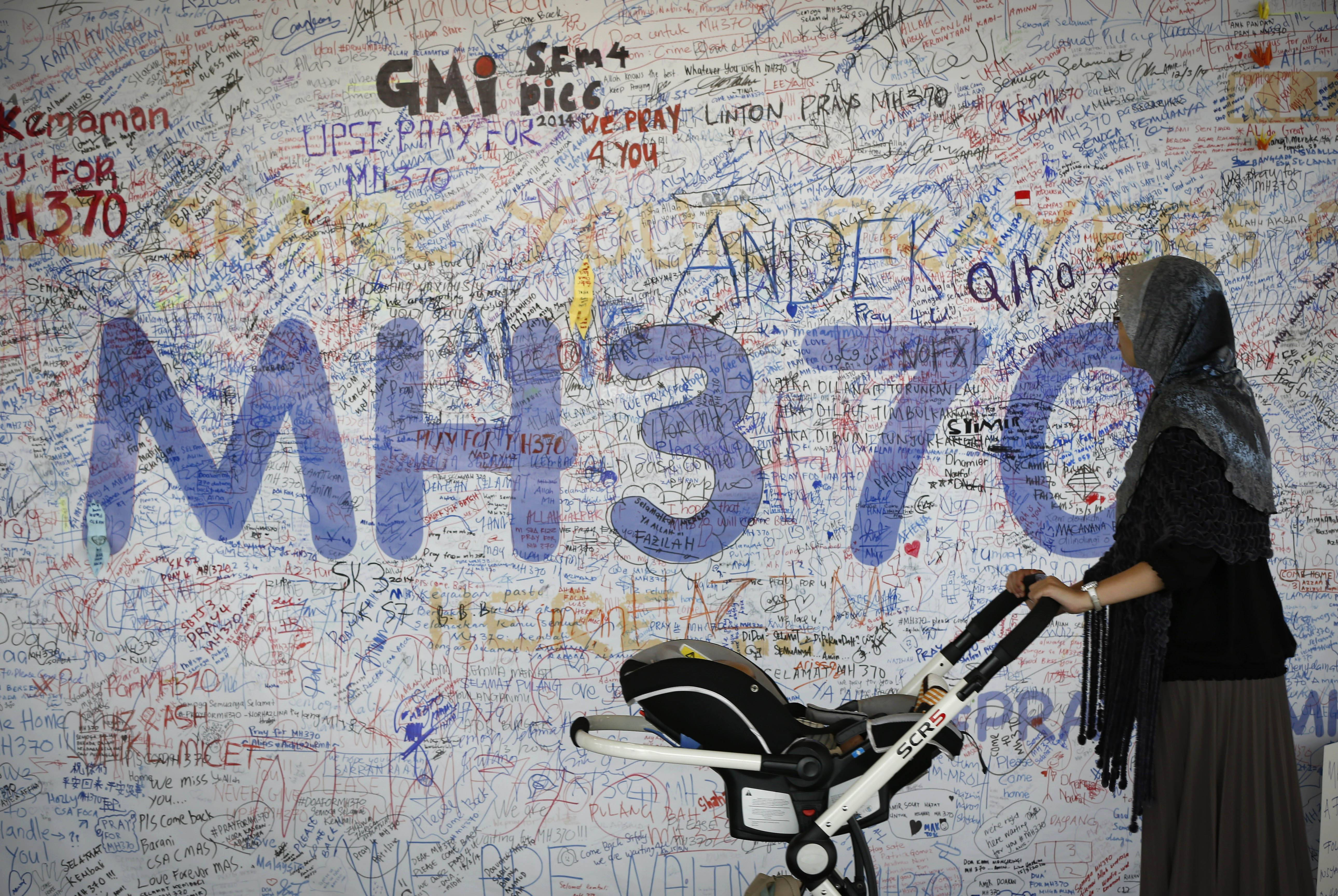 A woman pushes her baby cart in front of the messages board for passengers aboard a missing Malaysia Airlines plane at Kuala Lumpur International Airport in Sepang, Malaysia, Wednesday.