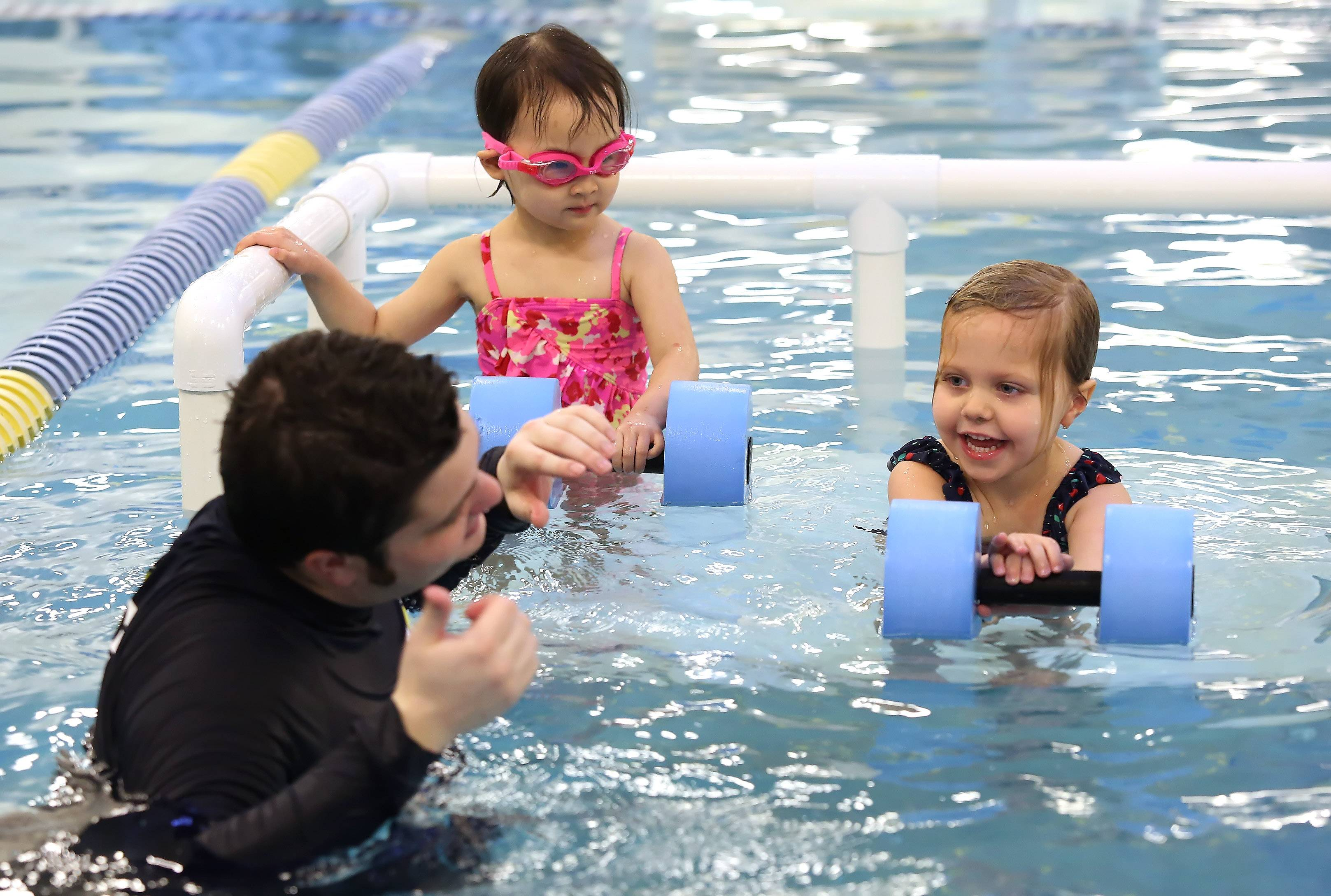 Youngsters Sarah Sapienza, 4, right, and Annabel Chung, 3, learn to swim from swim instructor Andy Jones at FOSS Swim School in Highland Park.
